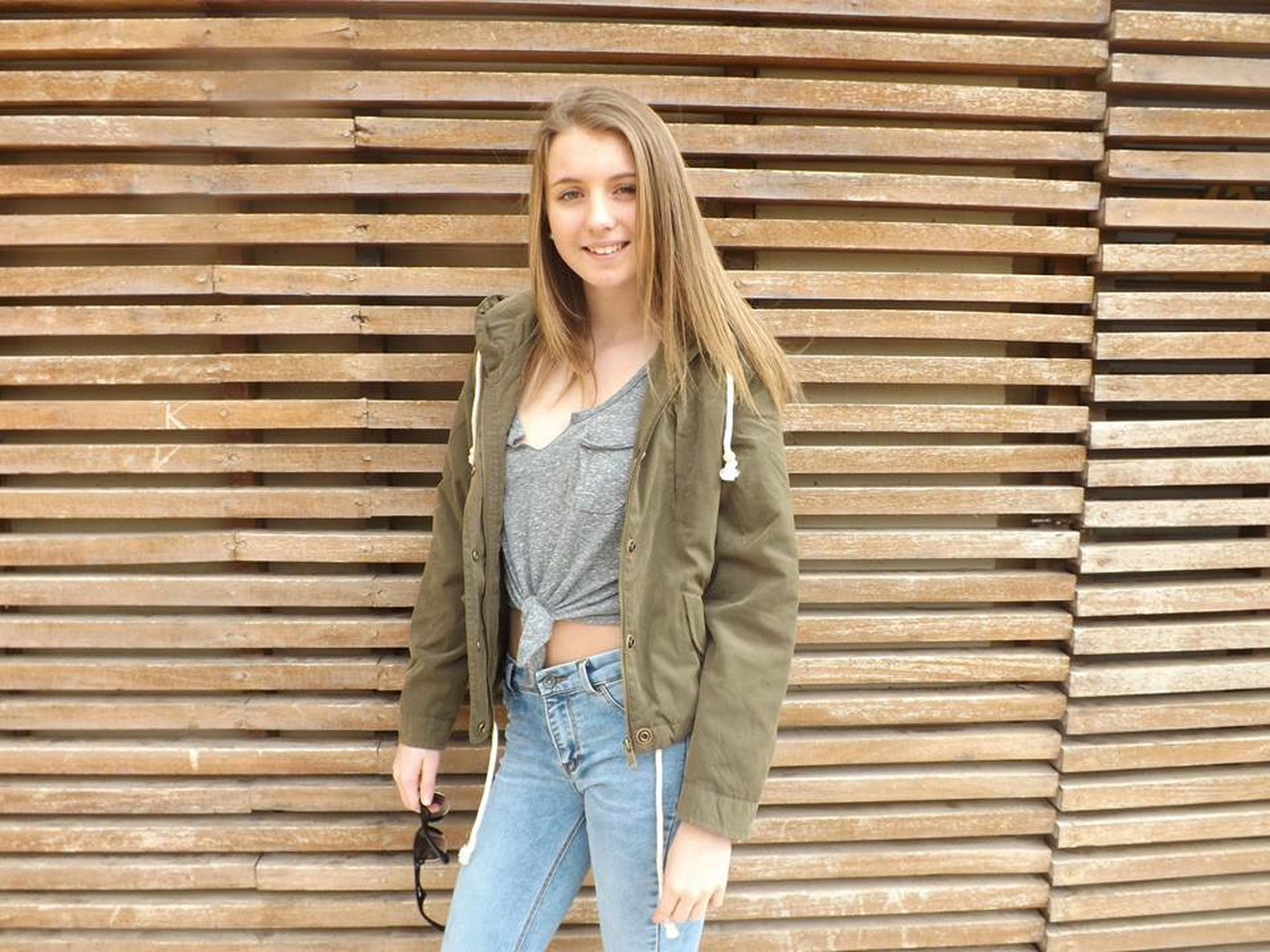 young adult, young women, looking at camera, front view, standing, person, portrait, casual clothing, lifestyles, three quarter length, brick wall, long hair, fashion, leisure activity, wall - building feature, fashionable