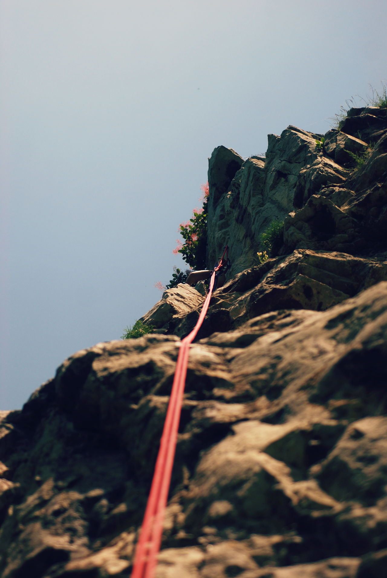 Low angle view - abseiling from a steep rock Abseiling Activity Adrenaline Adventure Altitude Belay Cliff Climber Climbing Descending Extreme Sports Lifestyle Low Angle View Mountain Mountain Climbing Mountaineering Rappel Rappelling Rock Climbing Rocks Rope Scenics Sky Steep Vertical
