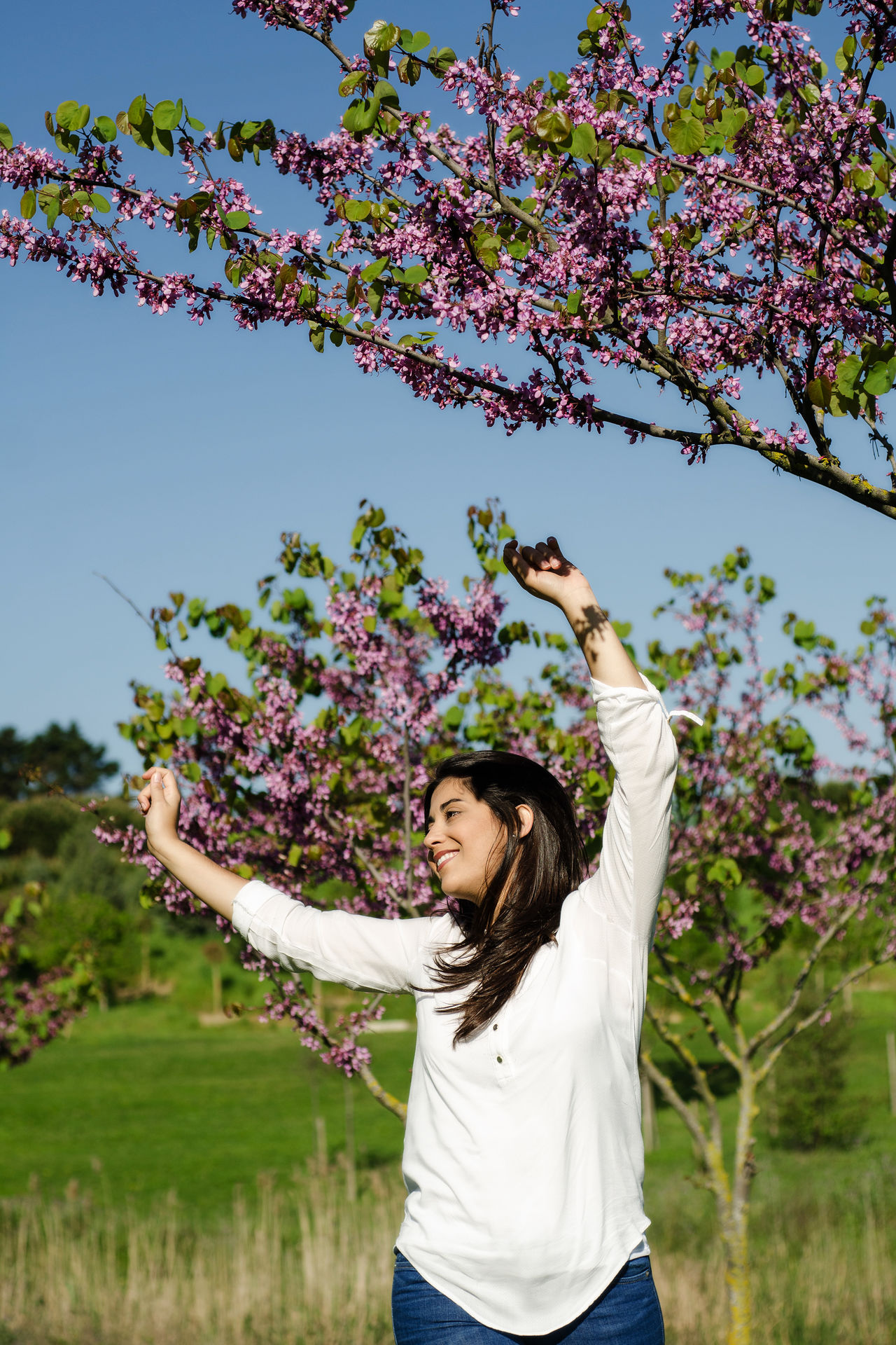 Woman happy with live, enjoy´s the spring the city park Beauty In Nature Blossom Branch Casual Clothing Day Flower Fragility Freshness Growth Leisure Activity Lifestyles Nature One Person Outdoors Plant Real People Sky Springtime Tree Women Young Adult Young Women