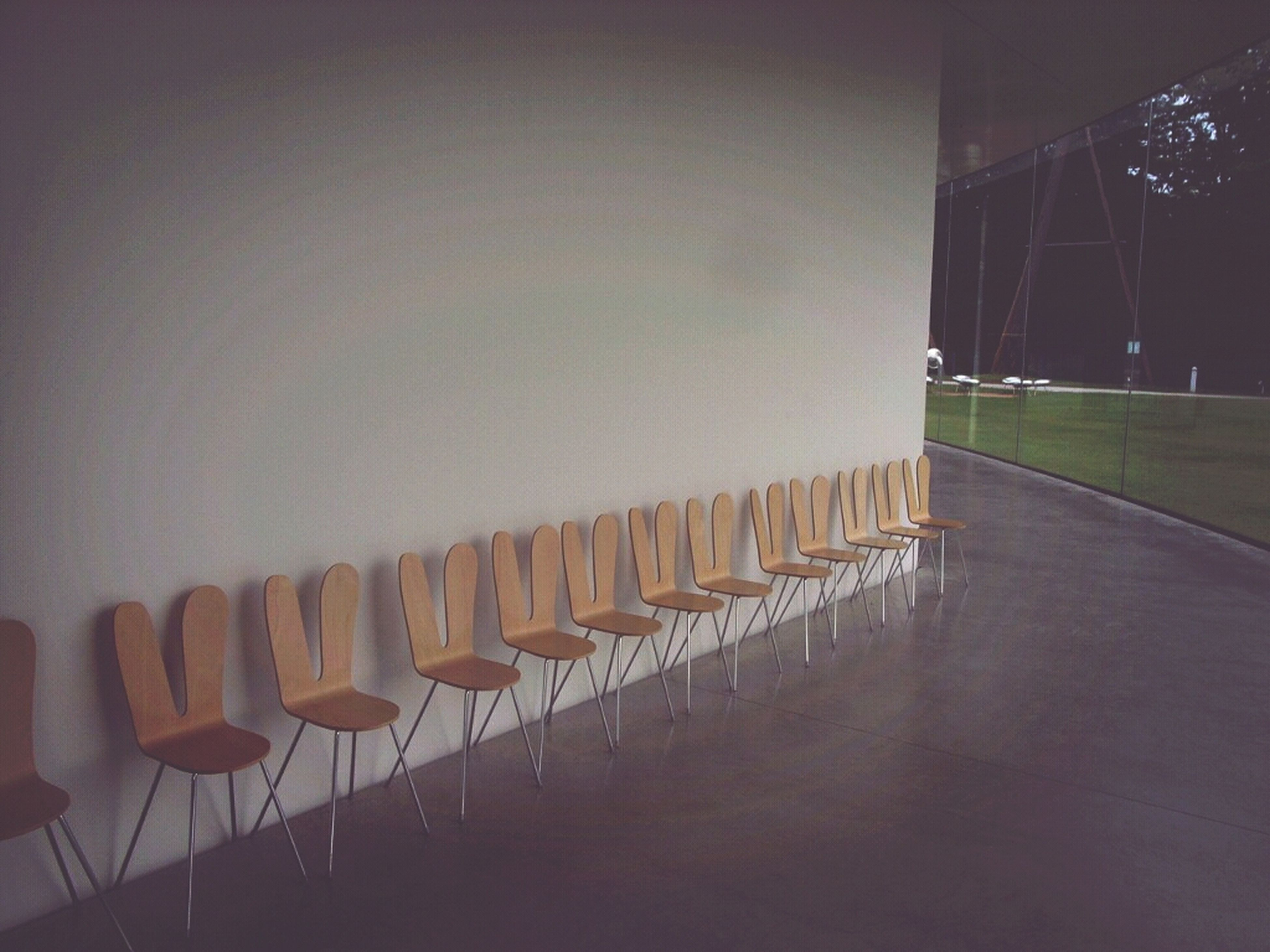 empty, in a row, illuminated, indoors, absence, lighting equipment, chair, built structure, night, architecture, seat, no people, repetition, electric light, copy space, wall - building feature, side by side, hanging, clear sky, shadow