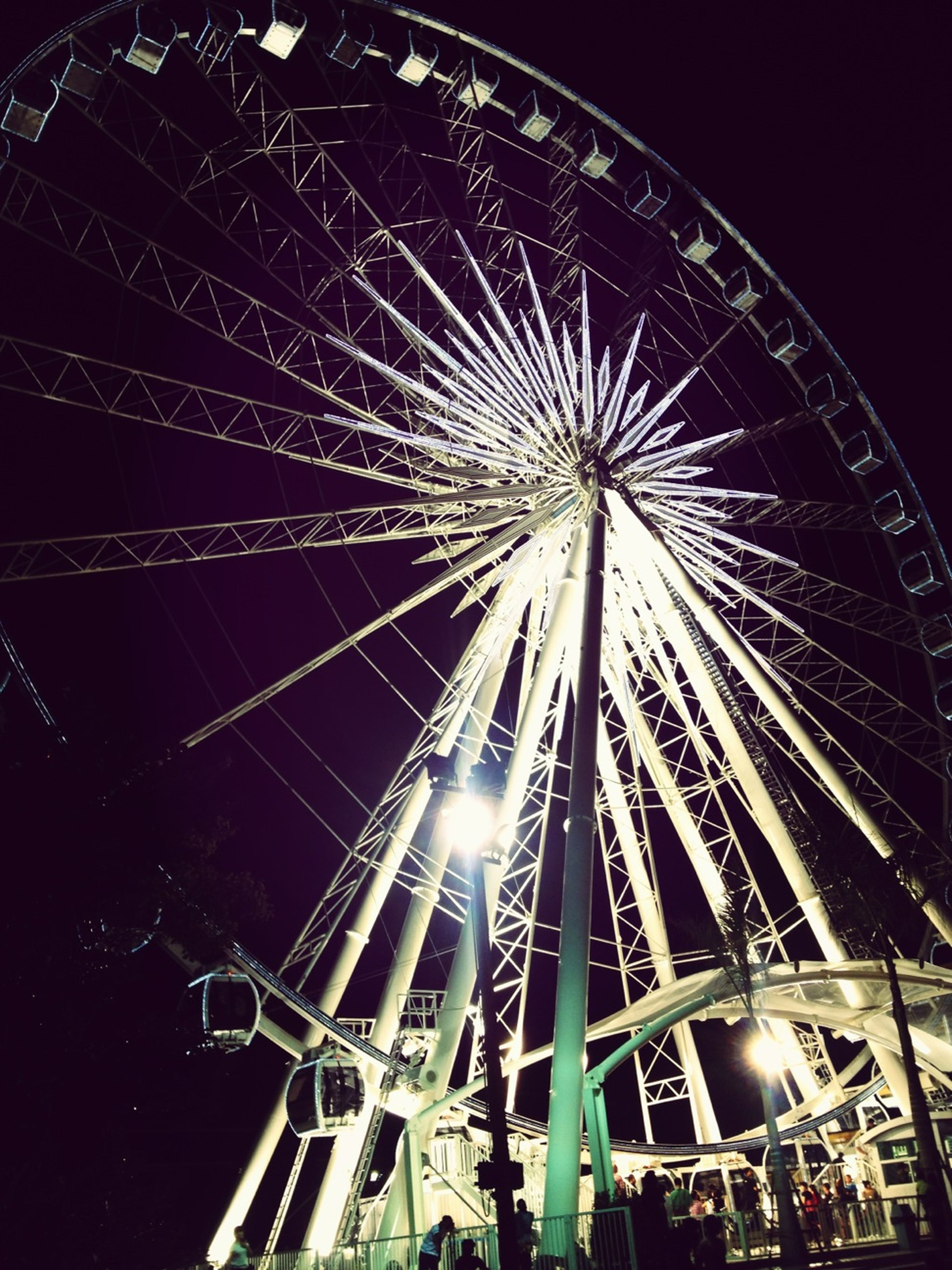 ferris wheel, amusement park ride, arts culture and entertainment, amusement park, low angle view, night, illuminated, built structure, architecture, sky, building exterior, traveling carnival, big wheel, clear sky, outdoors, travel destinations, no people, fun, celebration, city
