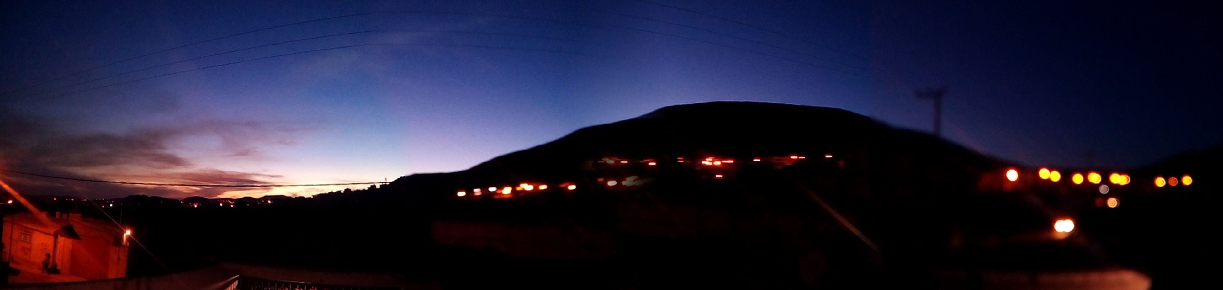 illuminated, night, sky, lighting equipment, silhouette, dusk, electricity, dark, blue, outdoors, light - natural phenomenon, mountain, copy space, landscape, glowing, scenics, nature, street light, no people, long exposure