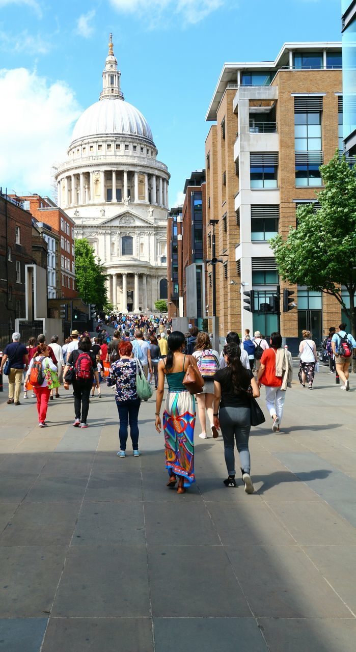 building exterior, architecture, built structure, walking, large group of people, real people, day, outdoors, city, sky, women, men, people