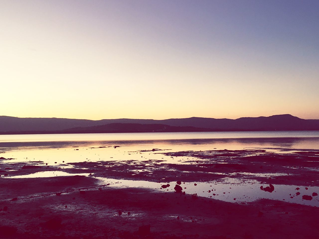 water, nature, sea, tranquility, scenics, tranquil scene, beauty in nature, silhouette, beach, copy space, sunset, clear sky, mountain, no people, outdoors, sky, travel destinations, day, salt - mineral