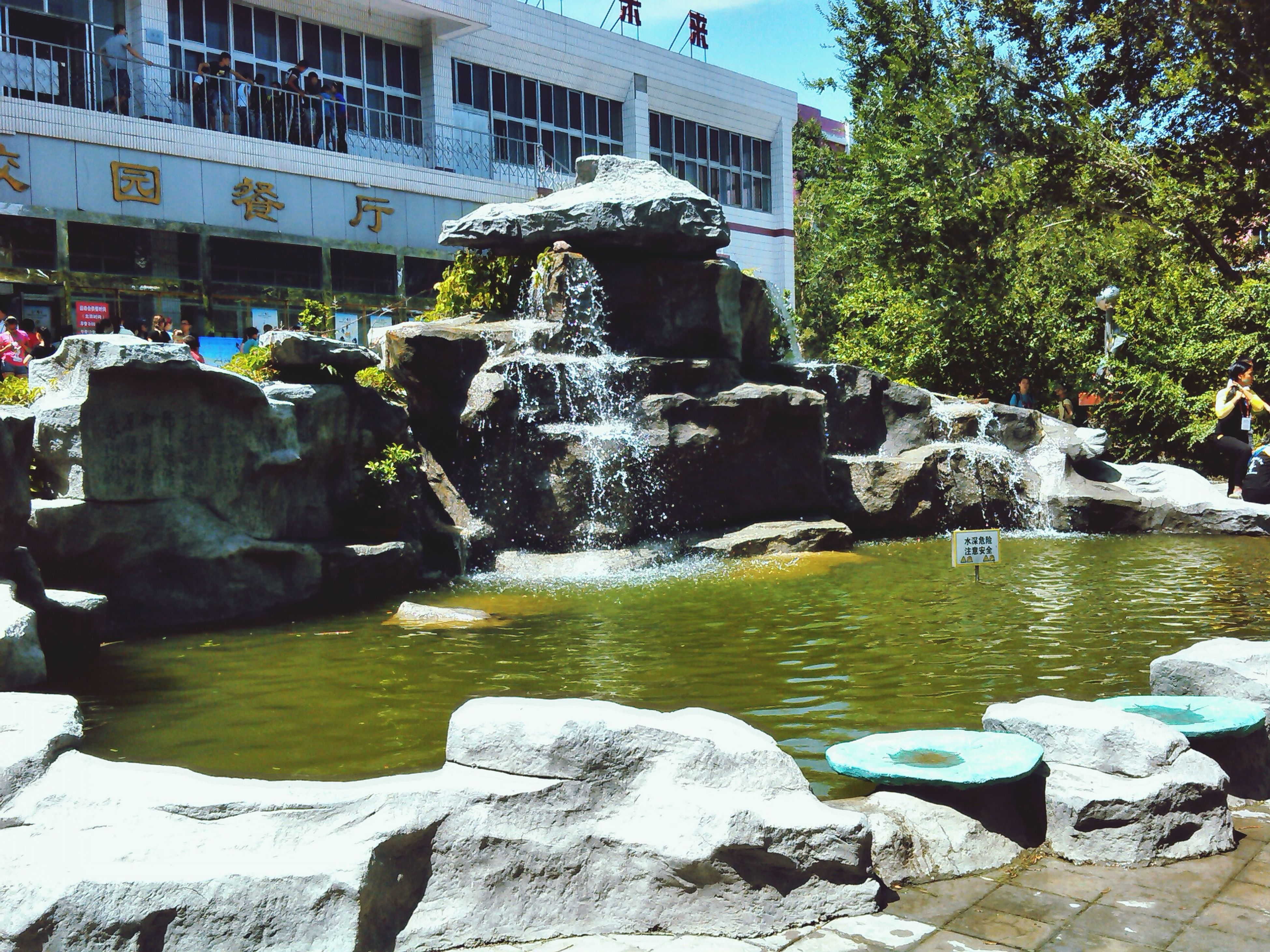 water, fountain, tree, built structure, sculpture, statue, architecture, flowing water, rock - object, park - man made space, incidental people, art and craft, flowing, motion, nature, art, human representation, building exterior, pond, day