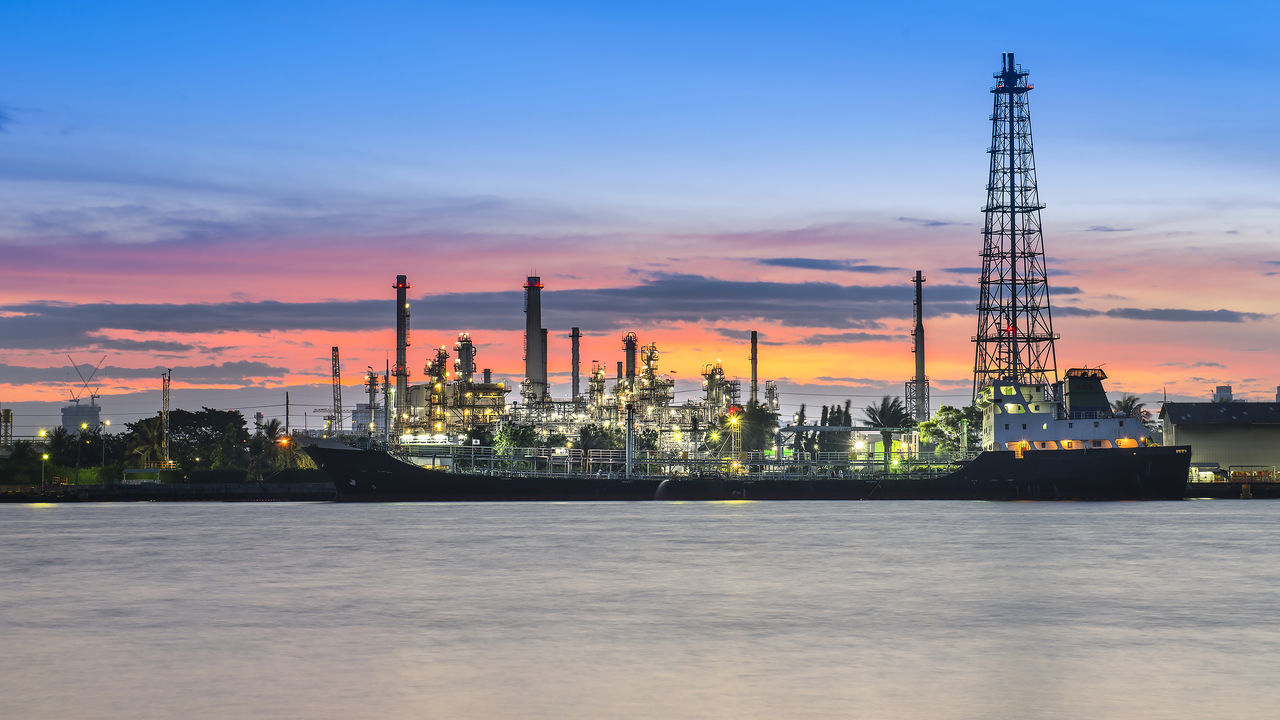 Oil refinery among grass at the early morning Business Business Finance And Industry Chemistry Engineering Environment Fuel And Power Generation Gas Gasoline Industry No People Oil Oil Industry Petrochemical Plant Refinery Sunset Technology Tower Water