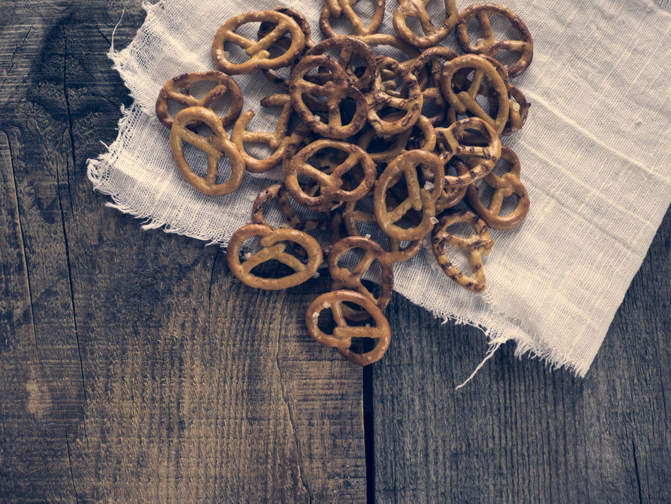 Heap of fresh Wheat salt pretzels on hessian linen fabric cloth and wooden table Circle Close-up Cloth Fabric Fresh Heap Hessian Linen Man Made Object Metal No People Pretzels Salt Surface Level Table Wheat Wooden