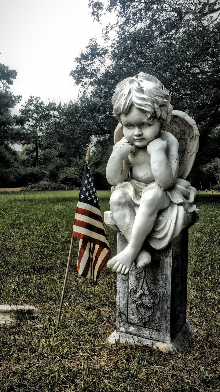 Angel Statue And American Flag In Graveyard
