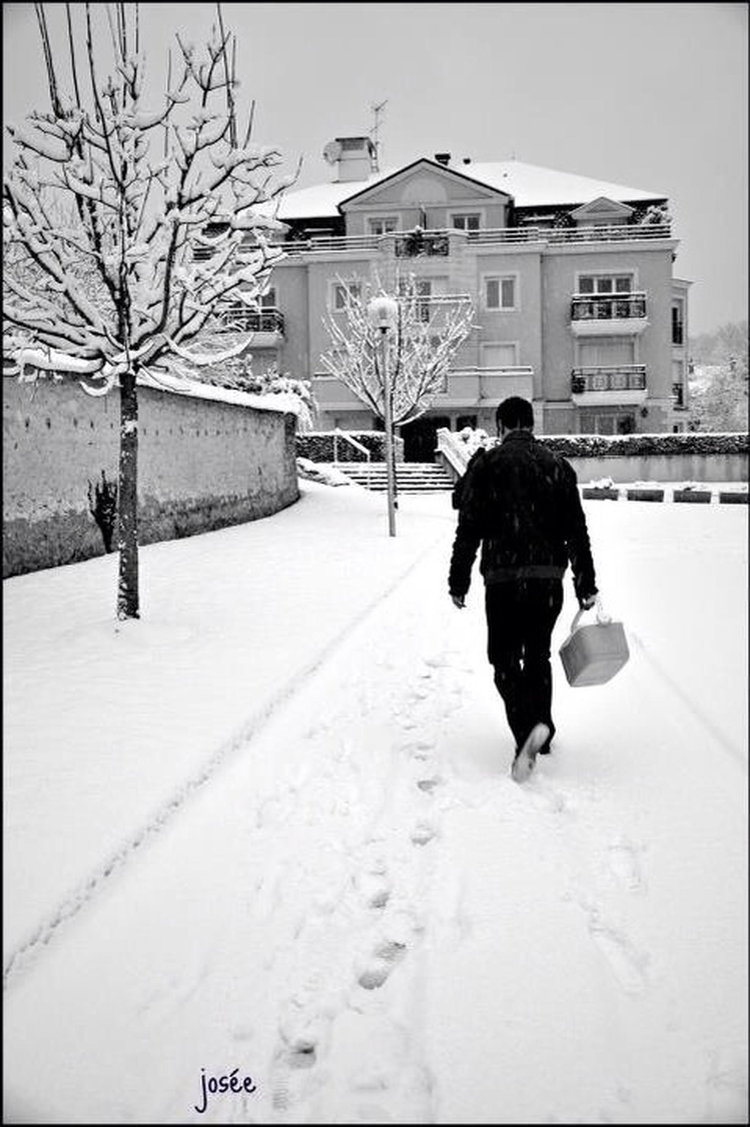 full length, walking, rear view, building exterior, architecture, built structure, lifestyles, winter, season, cold temperature, street, leisure activity, snow, the way forward, men, umbrella, city
