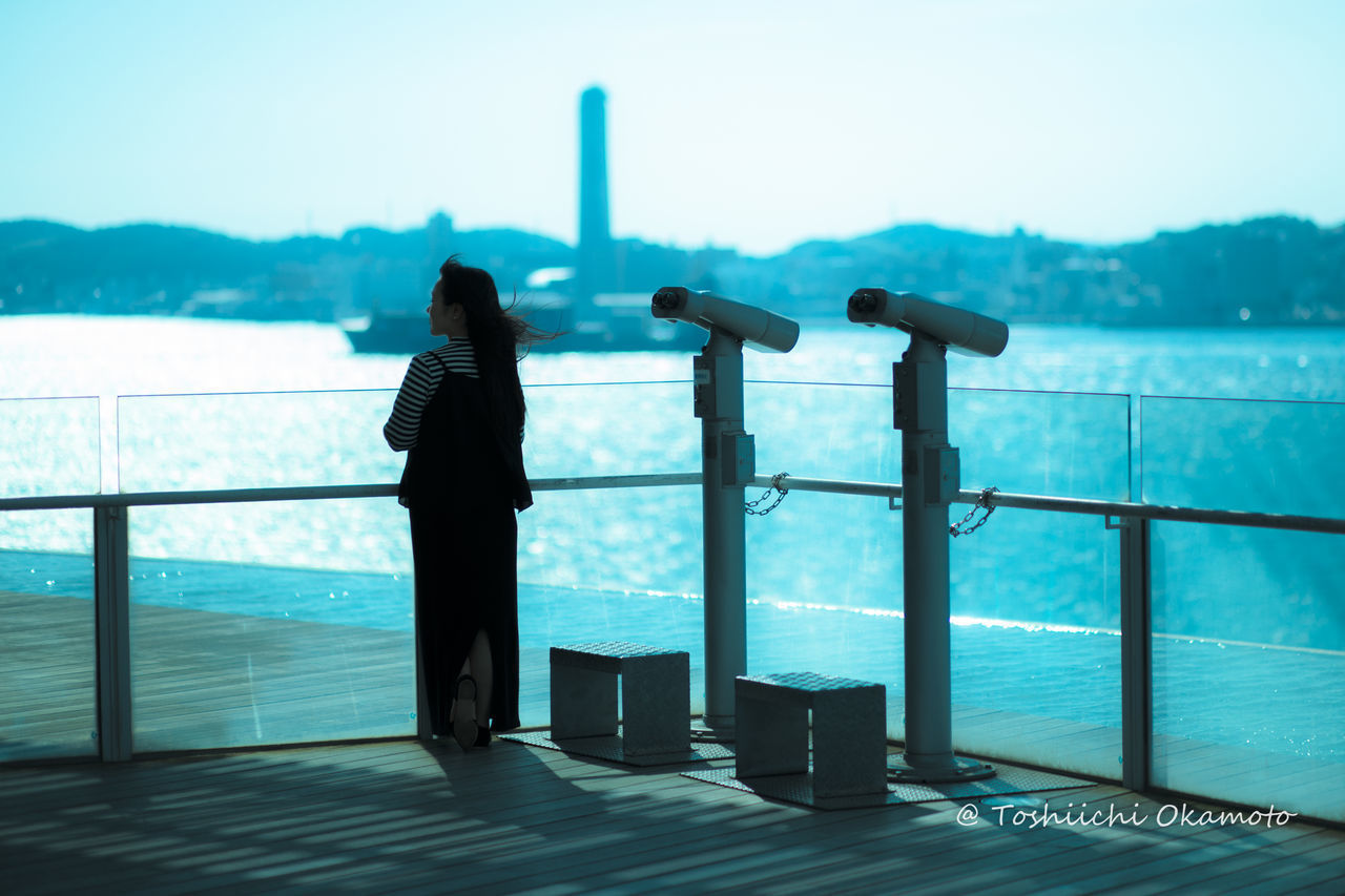 railing, sea, water, real people, one person, standing, observation point, coin-operated binoculars, day, leisure activity, scenics, looking at view, sky, full length, outdoors, nature, rear view, lifestyles, beauty in nature, women, travel destinations, horizon over water, vacations, mountain, young adult, people