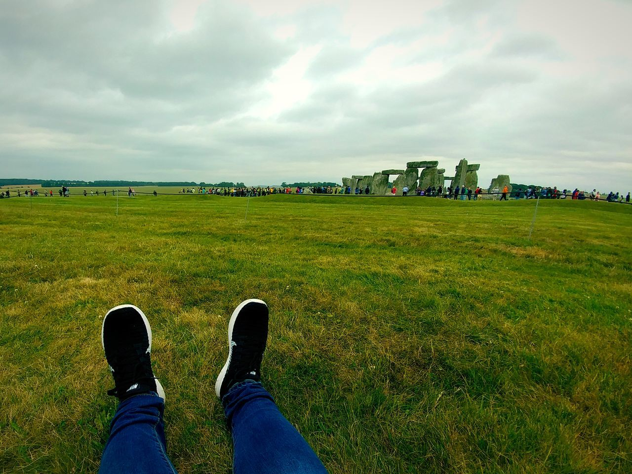 grass, cloud - sky, sky, real people, field, green color, day, nature, shoe, lifestyles, men, leisure activity, human leg, low section, outdoors, beauty in nature, standing, scenics, landscape, one person, people