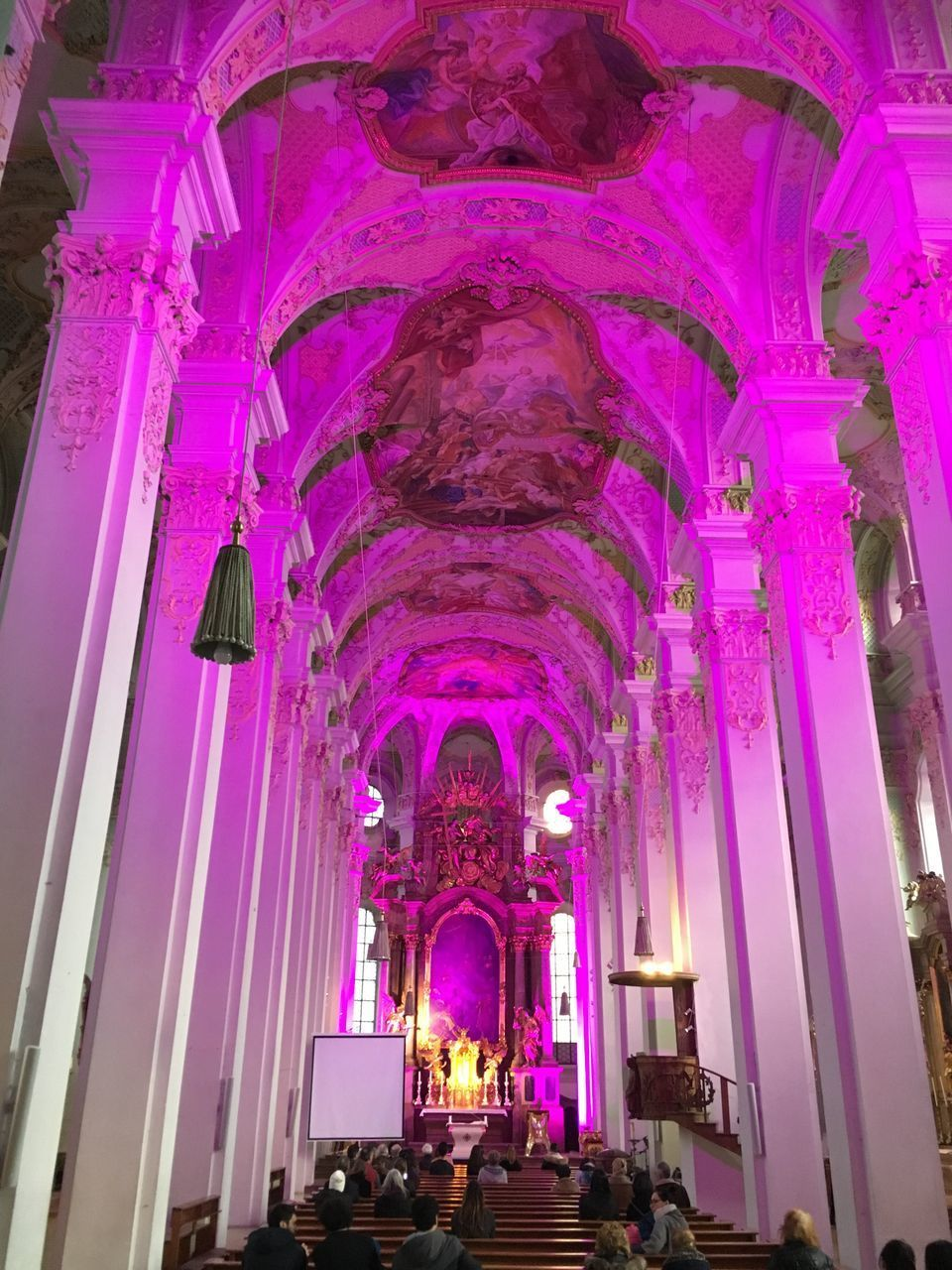 place of worship, religion, arch, low angle view, spirituality, indoors, architecture, purple, architectural column, built structure, illuminated, no people, day