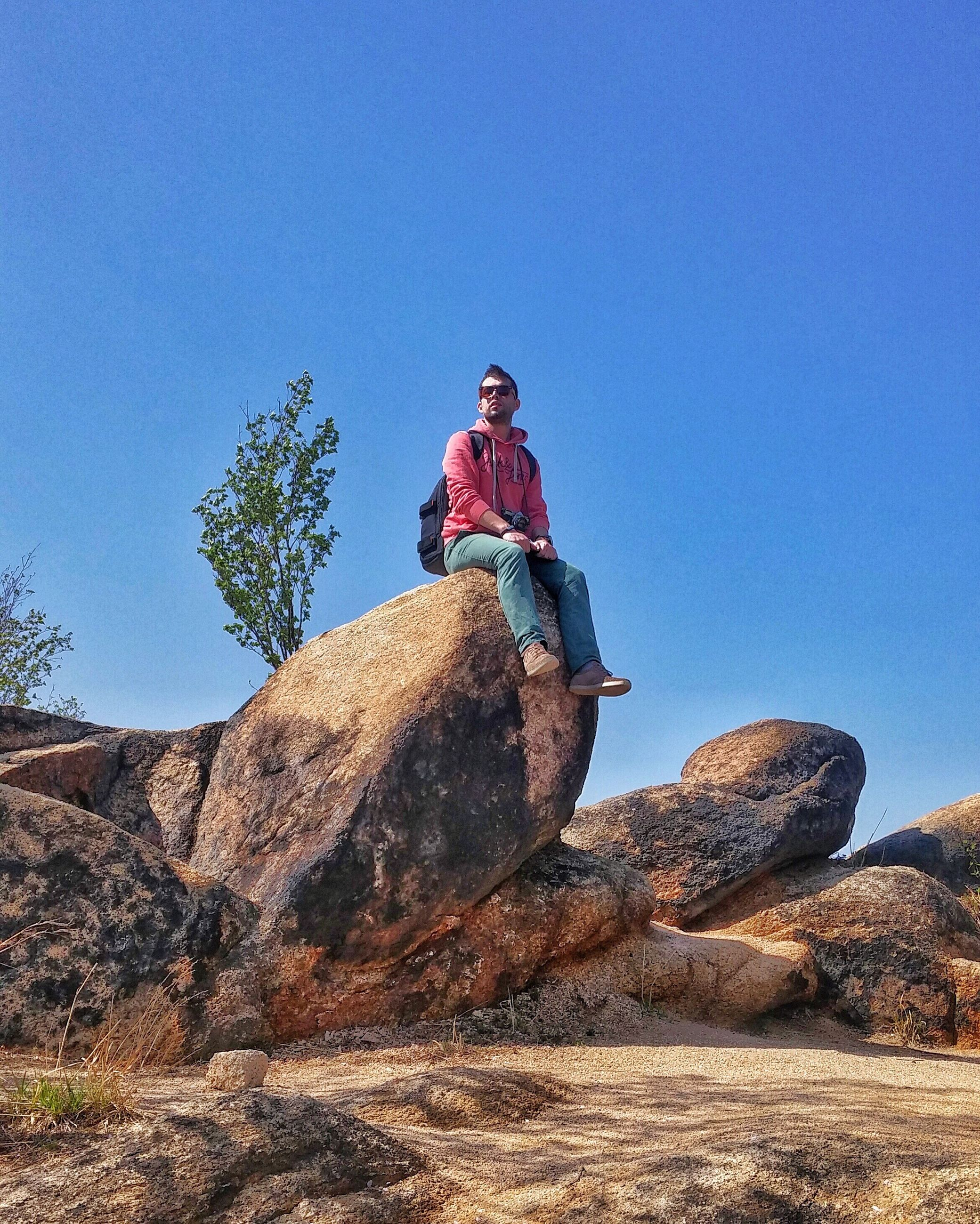 clear sky, leisure activity, blue, lifestyles, low angle view, full length, rock - object, copy space, men, adventure, nature, young adult, tranquility, rock formation, sky, sunlight, tree, young men