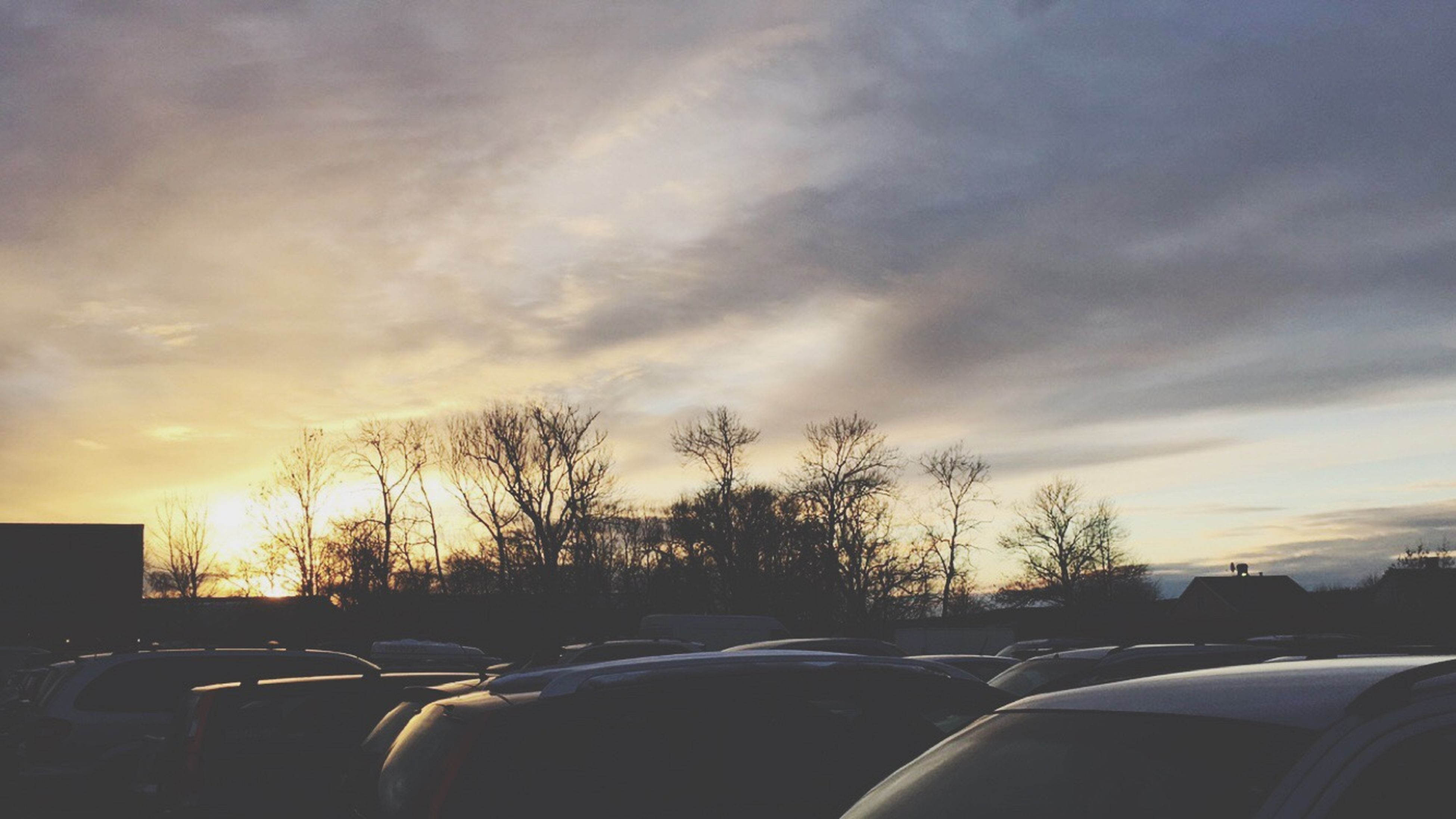 sunset, transportation, car, land vehicle, sky, cloud - sky, mode of transport, silhouette, road, tree, cloudy, street, bare tree, cloud, orange color, nature, beauty in nature, scenics, sun, outdoors