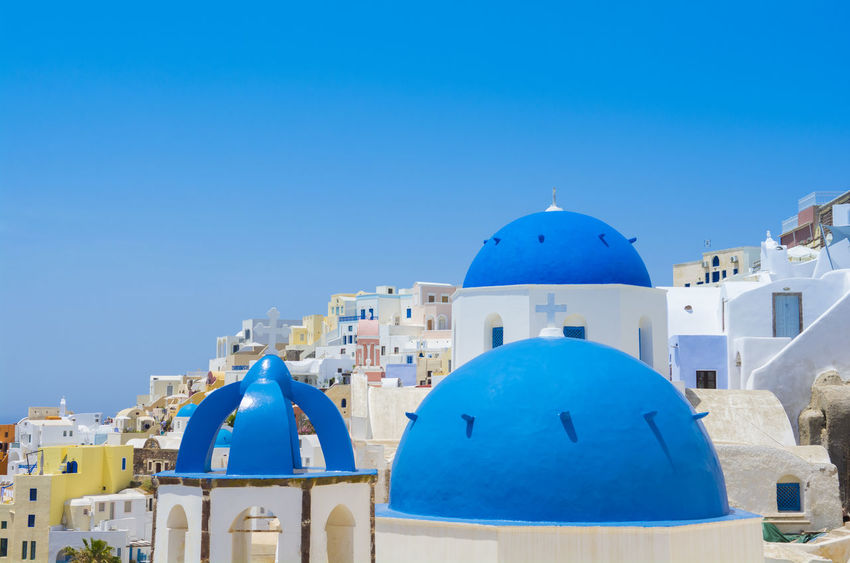 Santorini famous Orthodox church with blue domes in village Oia Aegean Sea Architecture Caldera Church Romantic Scenic Vacations Backgrounds Belfry Blue Colorful Cyclades Dome Honeymoon Idyllic Island Oia Religion Santorini Scenery Tourism Traditional Travel Destinations Vibrant Color Whitewashed