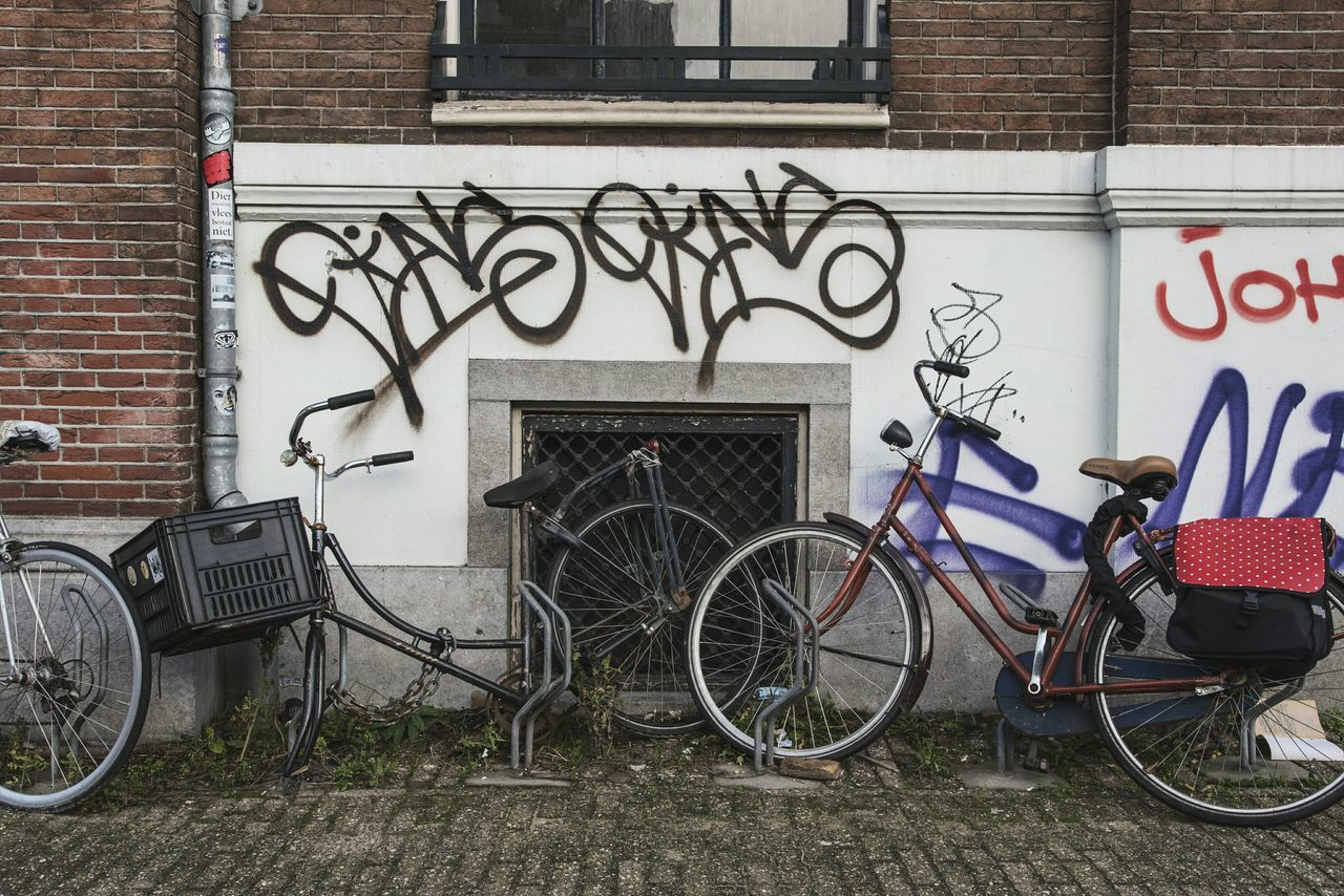 bicycle, transportation, building exterior, mode of transport, architecture, graffiti, built structure, stationary, outdoors, land vehicle, day, bicycle rack, no people, city