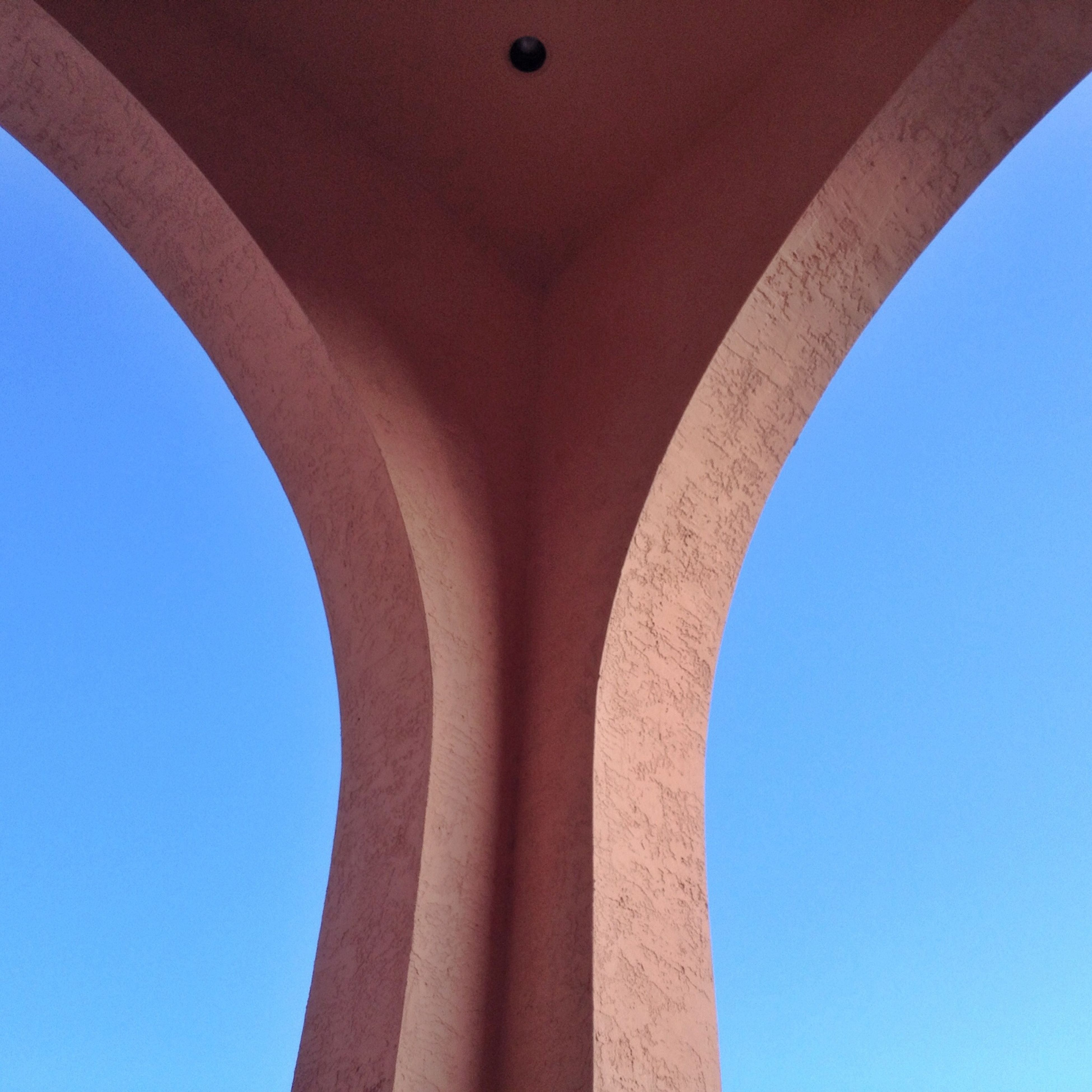 architecture, low angle view, built structure, clear sky, arch, blue, architectural column, column, day, sky, sunlight, architectural feature, no people, building exterior, part of, copy space, directly below, connection, outdoors