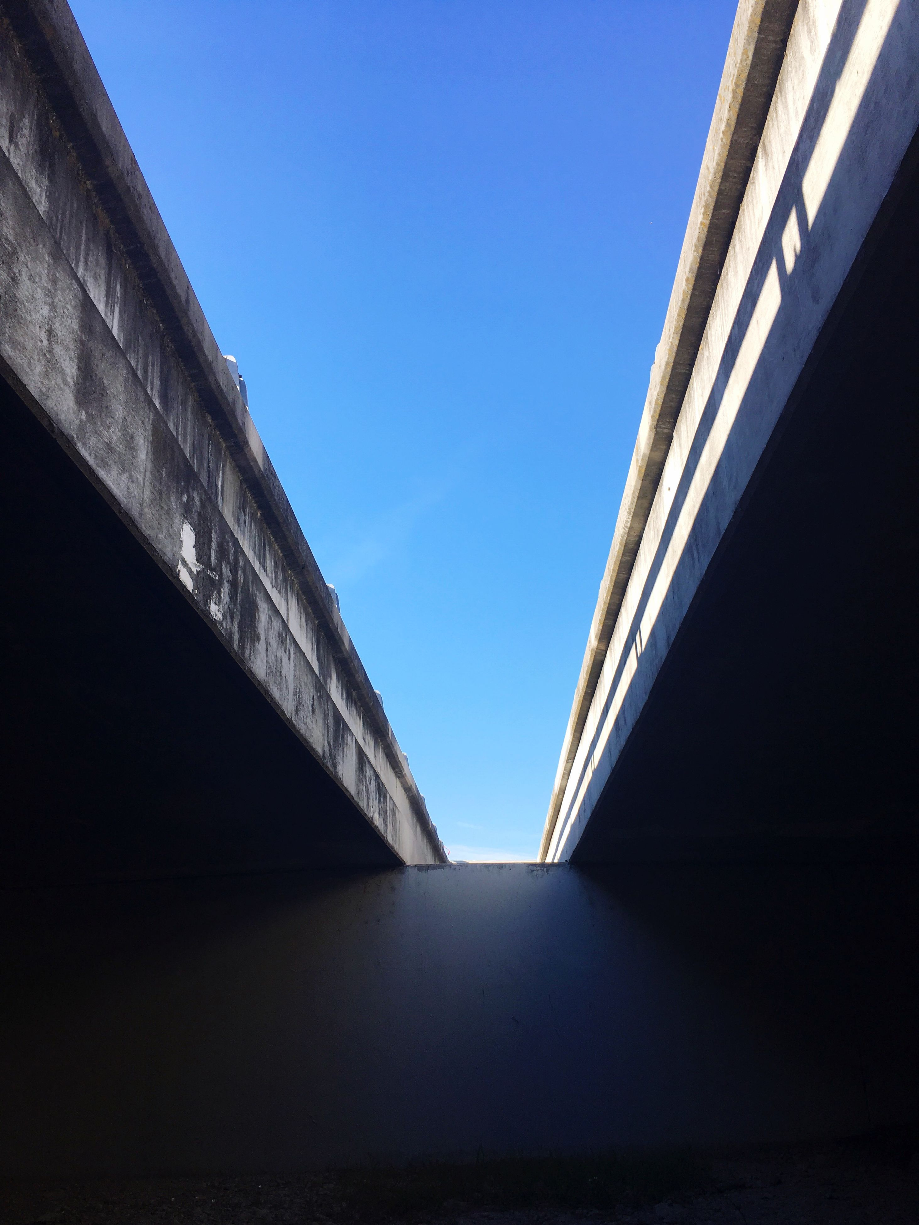 clear sky, architecture, low angle view, built structure, building exterior, blue, diminishing perspective, vanishing point, day, outdoors, the way forward, tall, no people, bridge, geometric shape
