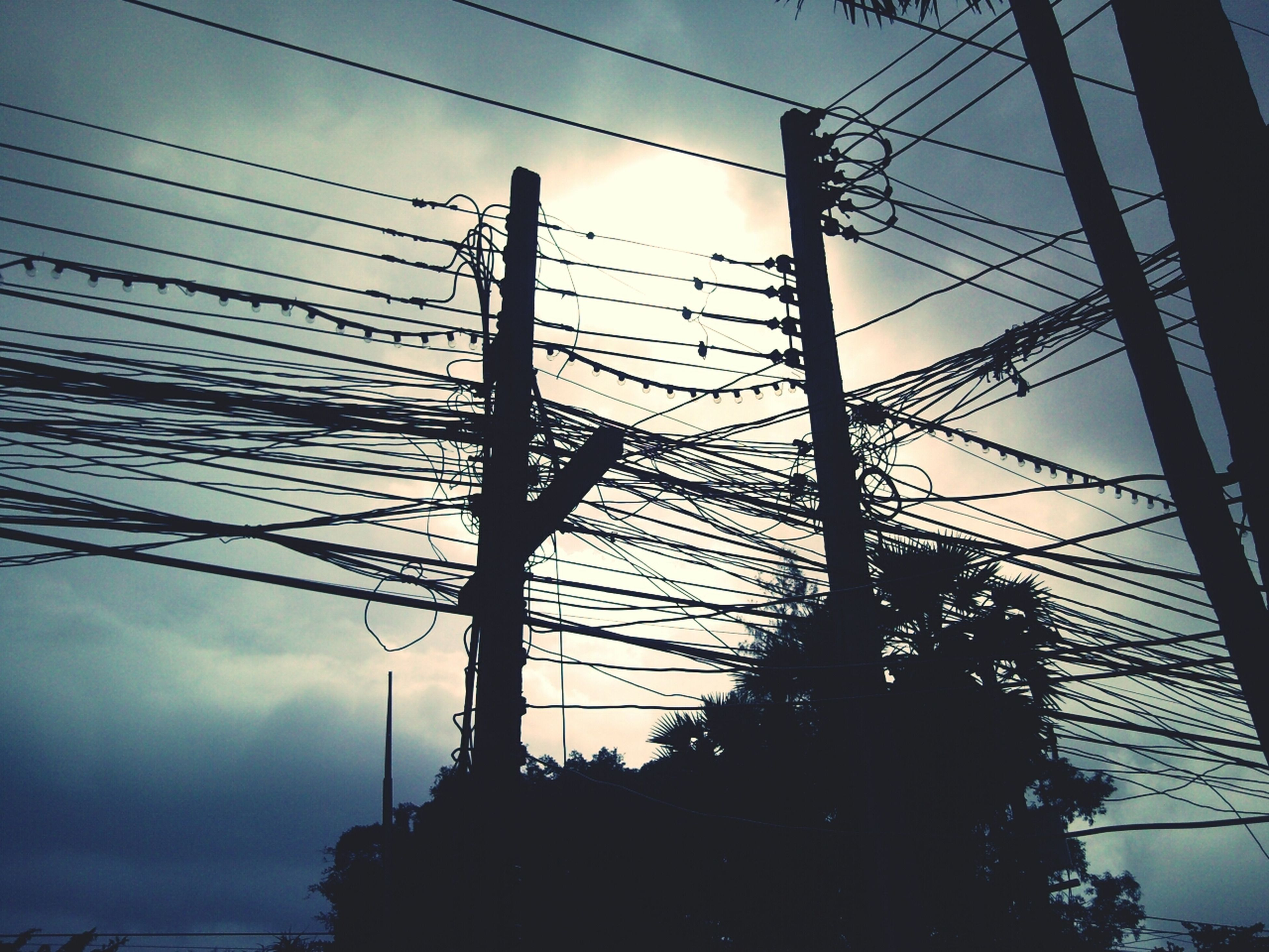 power line, low angle view, electricity pylon, power supply, electricity, cable, connection, sky, silhouette, fuel and power generation, power cable, technology, cloud - sky, built structure, sunset, cloud, dusk, architecture, tree, no people