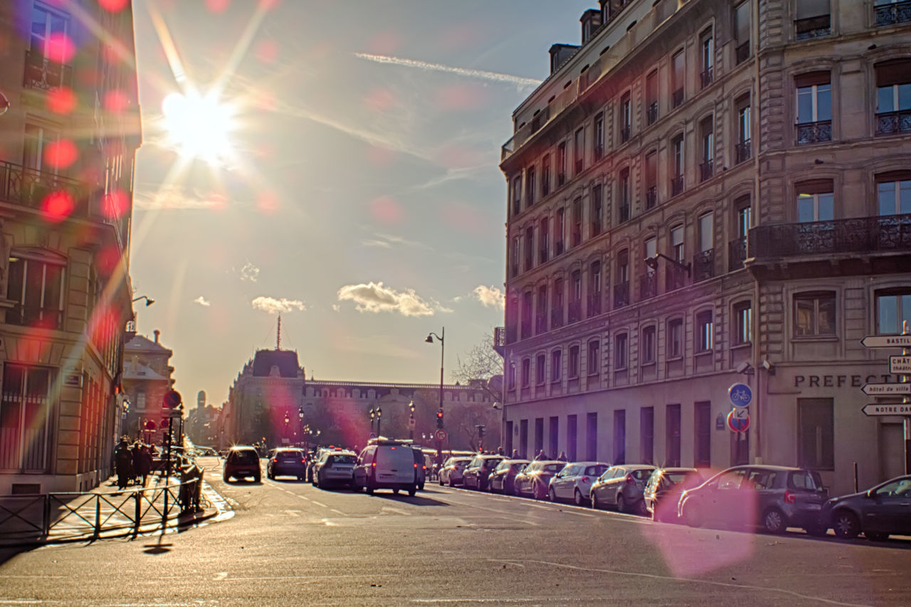 architecture, sunlight, lens flare, building exterior, sunbeam, sun, built structure, land vehicle, car, transportation, mode of transport, street, city, sky, outdoors, day, sunset, road, no people