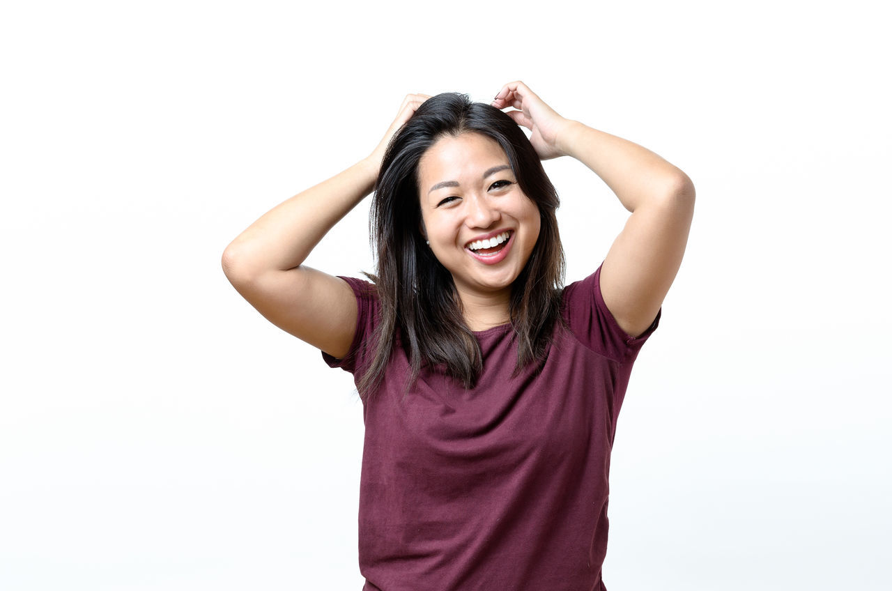 Arms Raised Beauty Carefree Casual Clothing Cheerful Enjoyment Excitement Females Front View Fun Happiness Human Arm Joy Looking At Camera One Person People Portrait Real People Relaxation Smiling Studio Shot Vitality White Background Young Adult Young Women