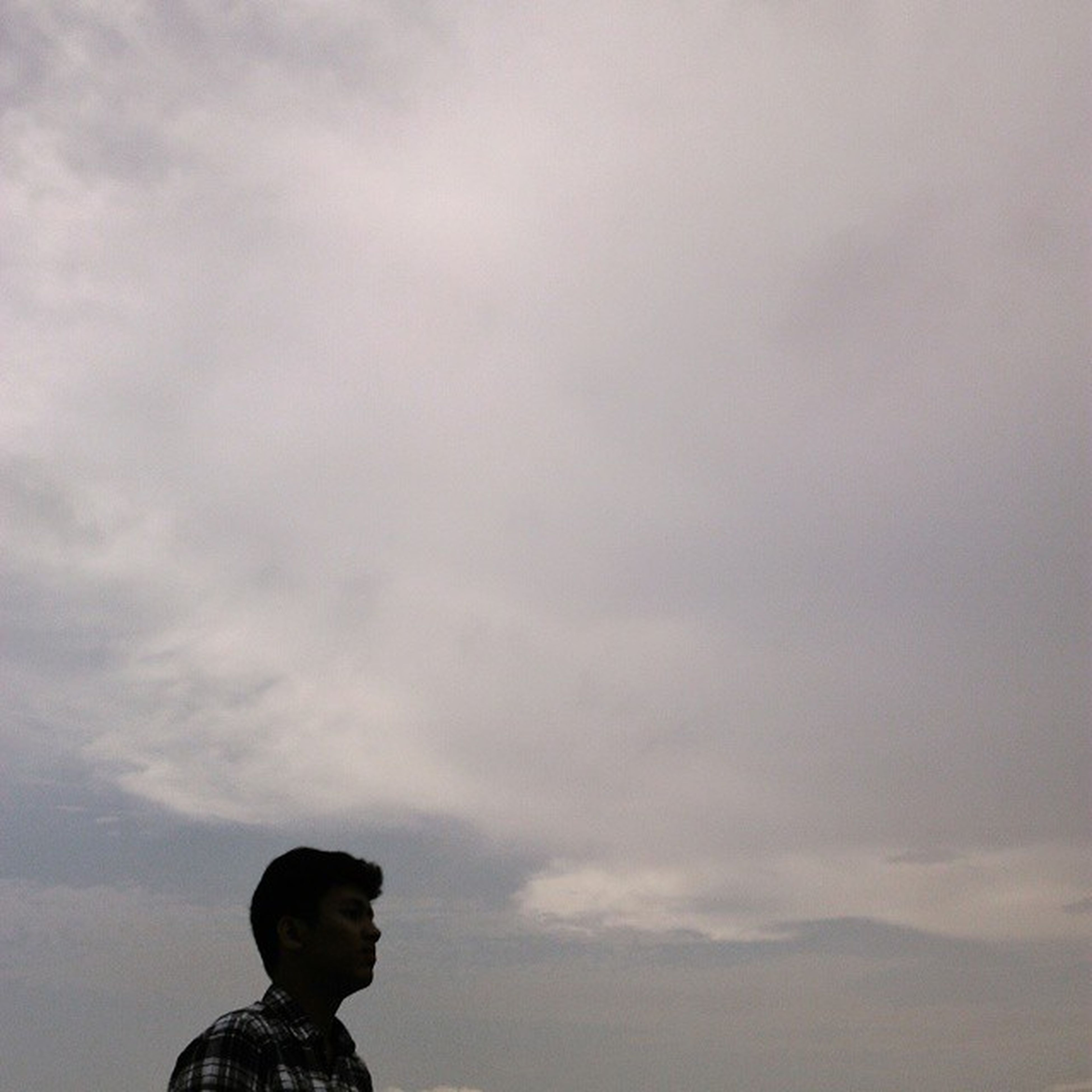 sky, lifestyles, leisure activity, cloud - sky, low angle view, headshot, person, cloudy, waist up, standing, young adult, looking at camera, young men, outdoors, childhood, three quarter length, happiness, portrait
