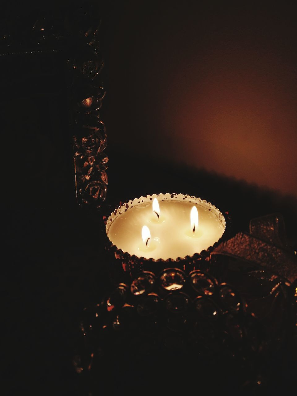 Close-Up Of Illuminated Candles In Container