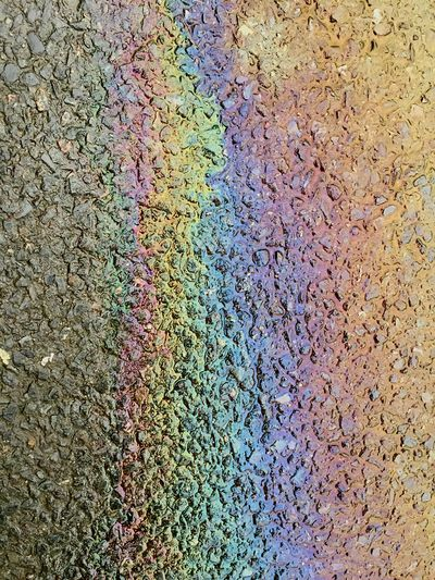 Oil slick rainbow on road Multi Colored Oil Spill Day Gasoline No People Leaking Close-up Road Outdoors Refueling Rainbow