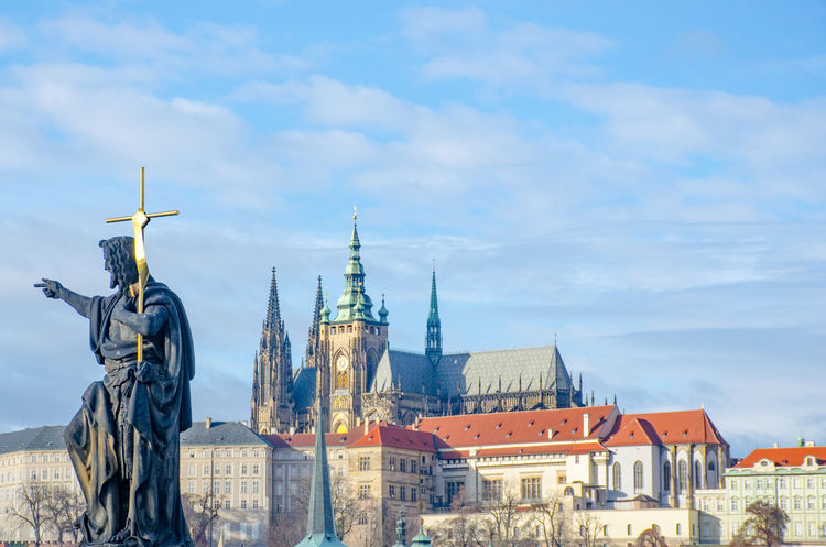 Statue with Cross overlooking Charles Bridge and St Vitus Cathedral Charles Bridge Cross Prague Architecture Building Exterior Built Structure Citiscape  Human Representation Religous Sculpture Statue
