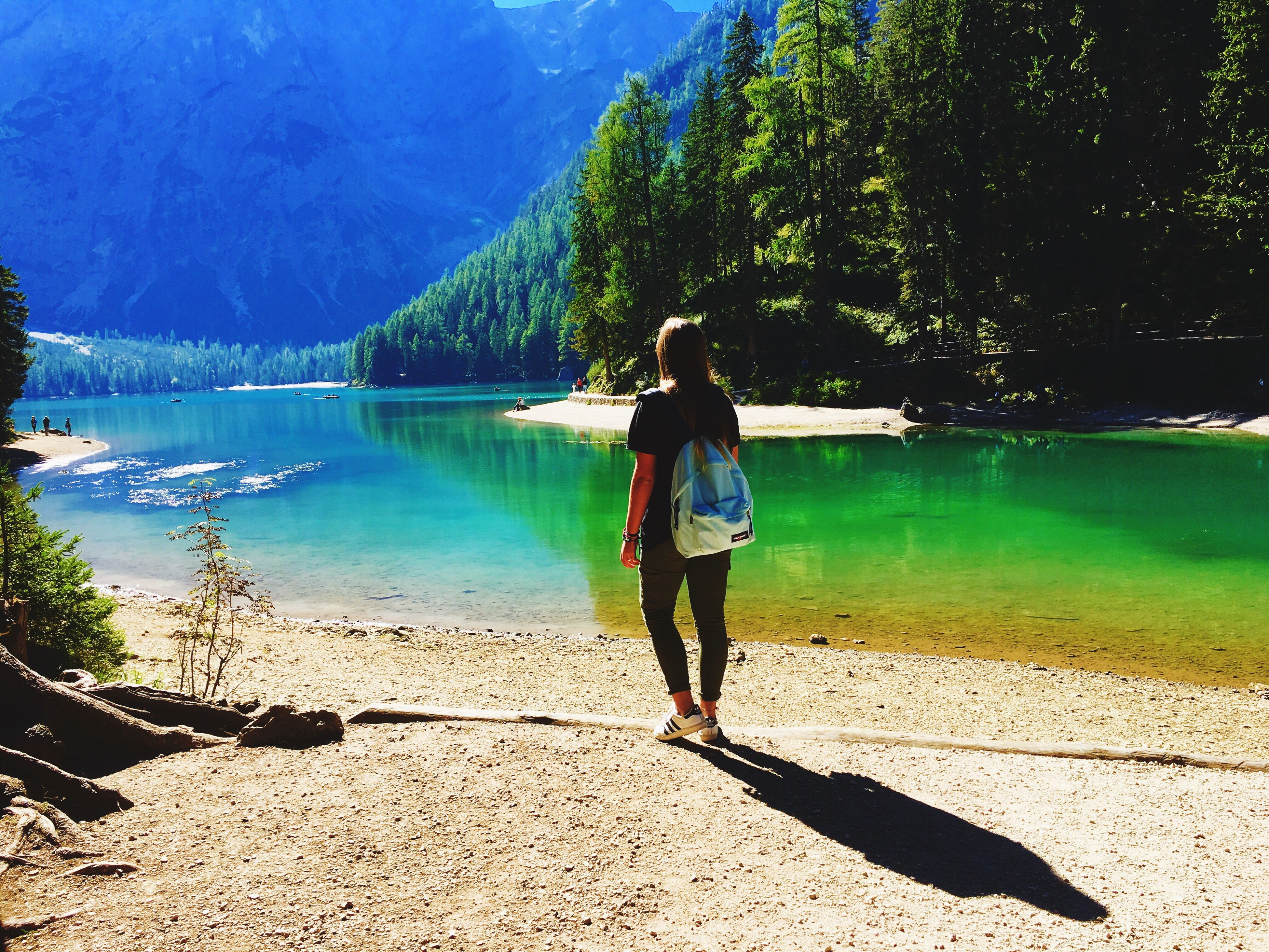 water, shadow, full length, rear view, lake, sunlight, tranquil scene, tree, tranquility, scenics, mountain, nature, calm, lakeside, beauty in nature, blue, solitude, alone, green color, getting away from it all, vacations, escapism, outdoors, majestic, day, weekend activities, standing water
