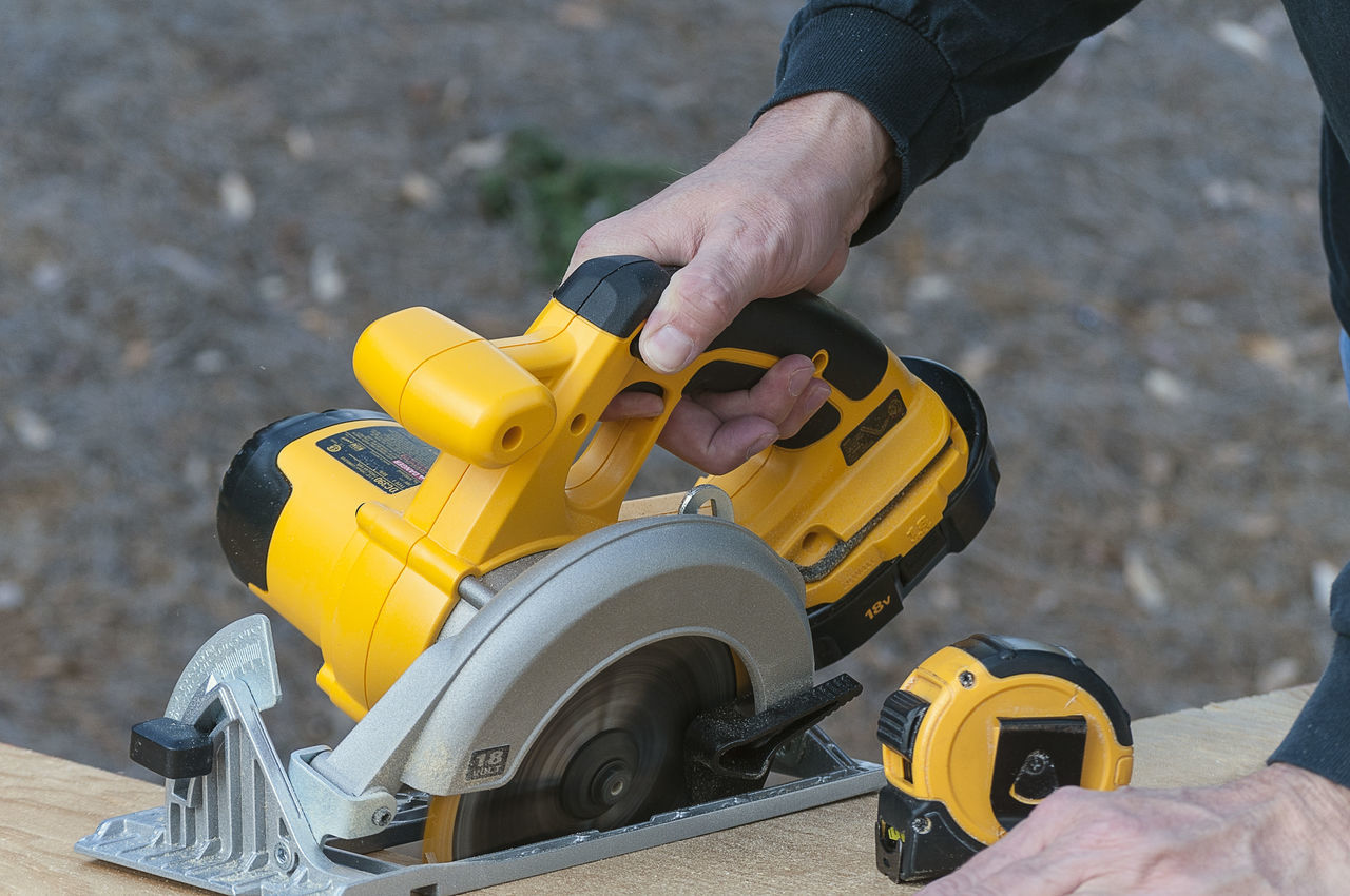 Holding A Yellow Circular Saw Cutting Wood Blade Carpentry Circulr Close-up Construction Cutting Hand Hand Tool Human Hand Plywood Power Power Tools Saw Tape Measure Tool Wood Work