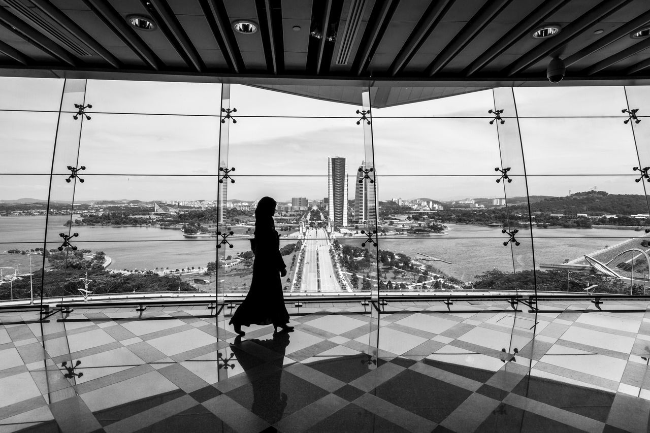 Silhouette of a woman walking inside the Putrajaya International Convention Centre with glass walls at the back showing the cityscape of Putrajaya Alone Architecture B&w Black And White Blackandwhite City Cityscape Futuristic Glass Wall Interior Lakes  Modern Architecture Muslim One Woman Only Putrajaya International Convention Centre Silhouette Sky Streetphotography Urban Urbanphotography Walking Woman
