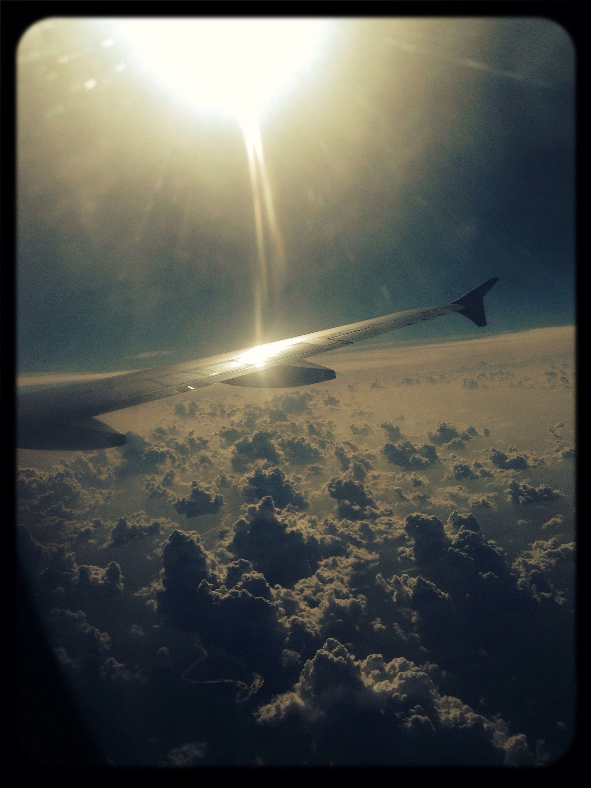 transfer print, auto post production filter, sun, aircraft wing, airplane, scenics, tranquil scene, beauty in nature, flying, tranquility, transportation, sky, nature, air vehicle, landscape, sunlight, sunbeam, aerial view, lens flare, travel