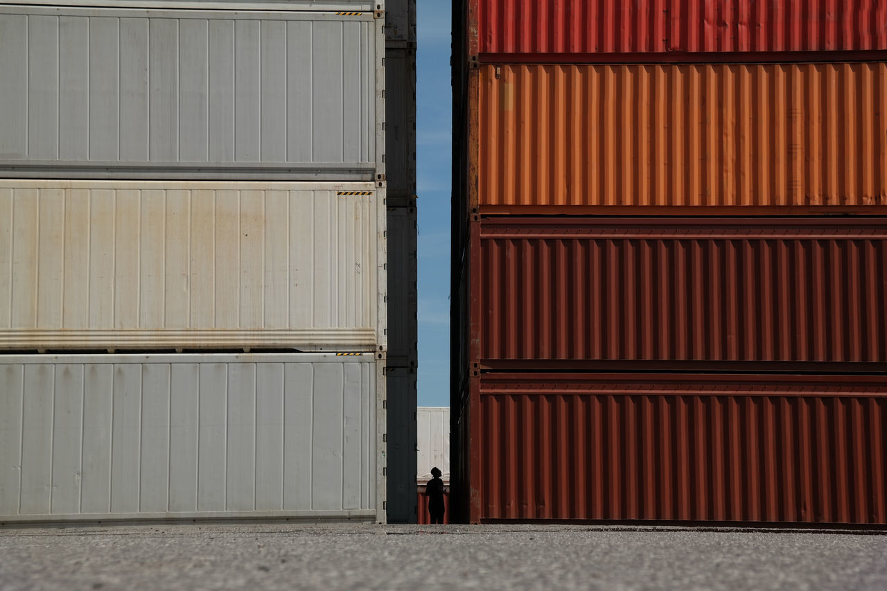 Blue Sky Business Business Finance And Industry Cargo Cargo Container Commerce Exploring Freight Gap Harbor Industrial One Person Outdoors Shipping  Silhouette Stacks  Terminal Trade