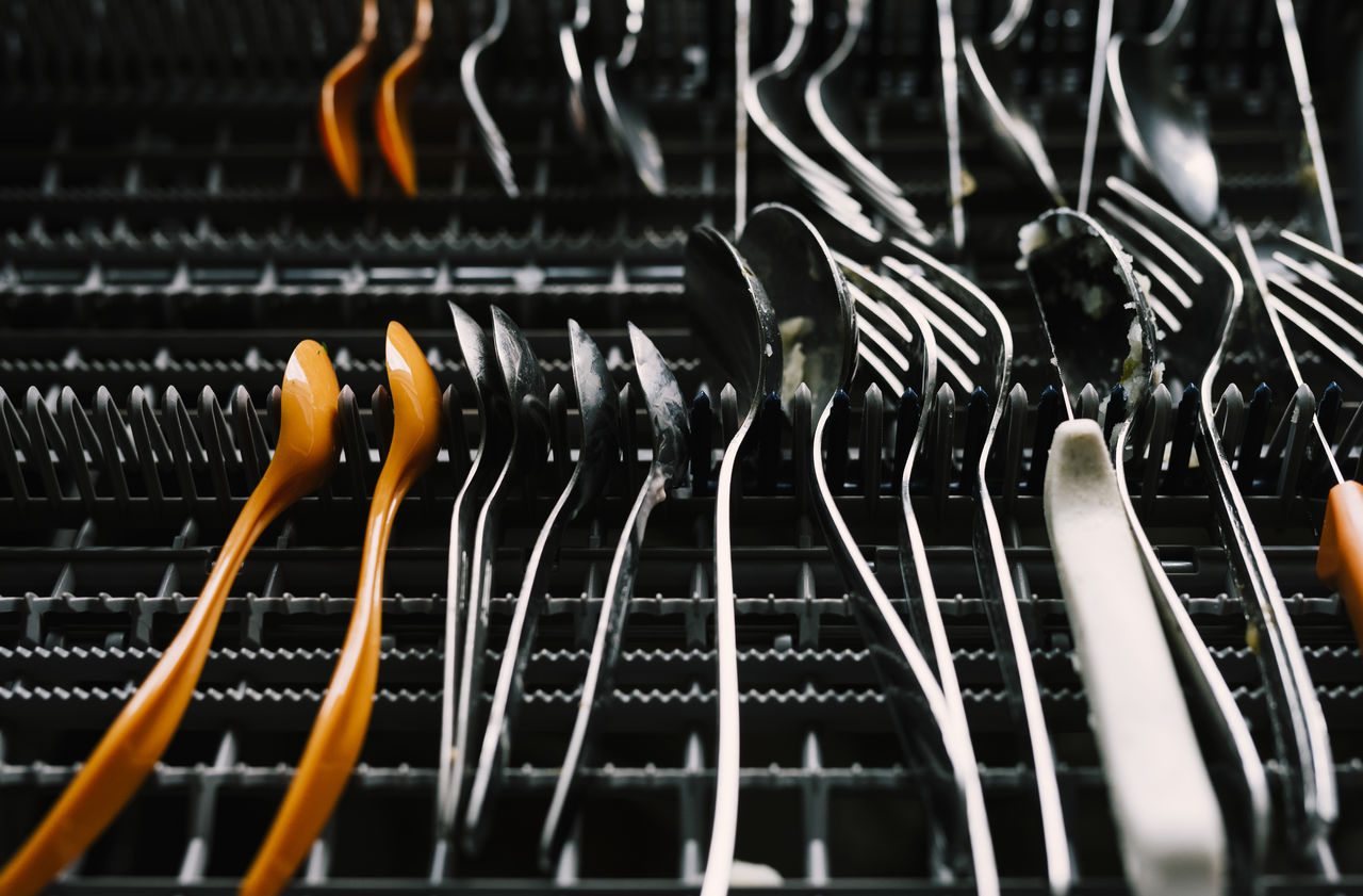 Close-Up Of Cutlery Arranging In Rack