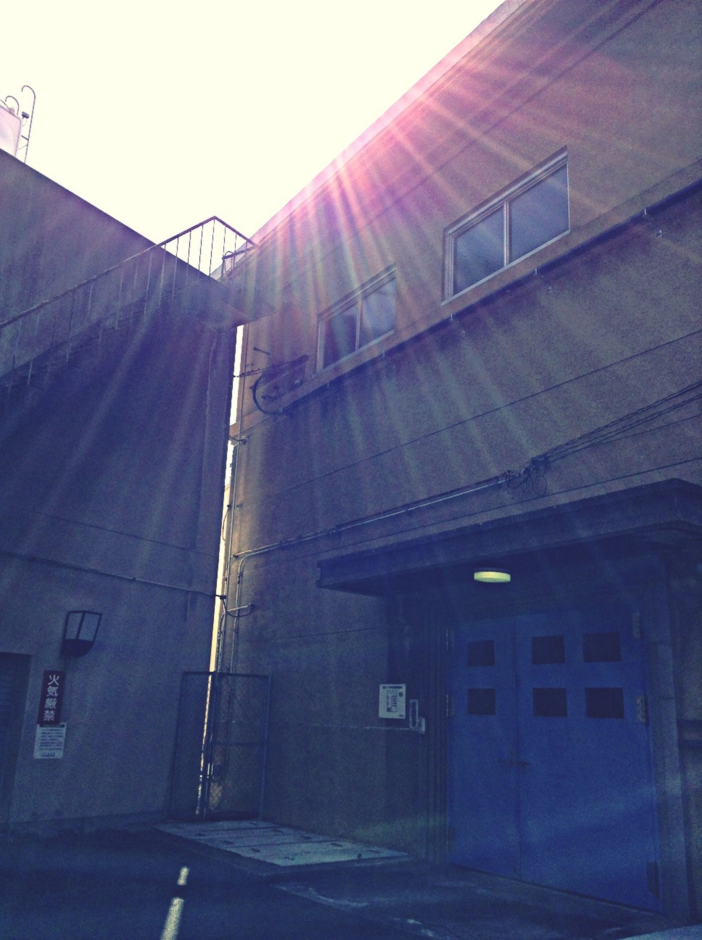 architecture, built structure, building exterior, sunlight, low angle view, transportation, the way forward, sun, clear sky, sunbeam, building, sky, lens flare, diminishing perspective, power line, no people, day, outdoors, street, sunny