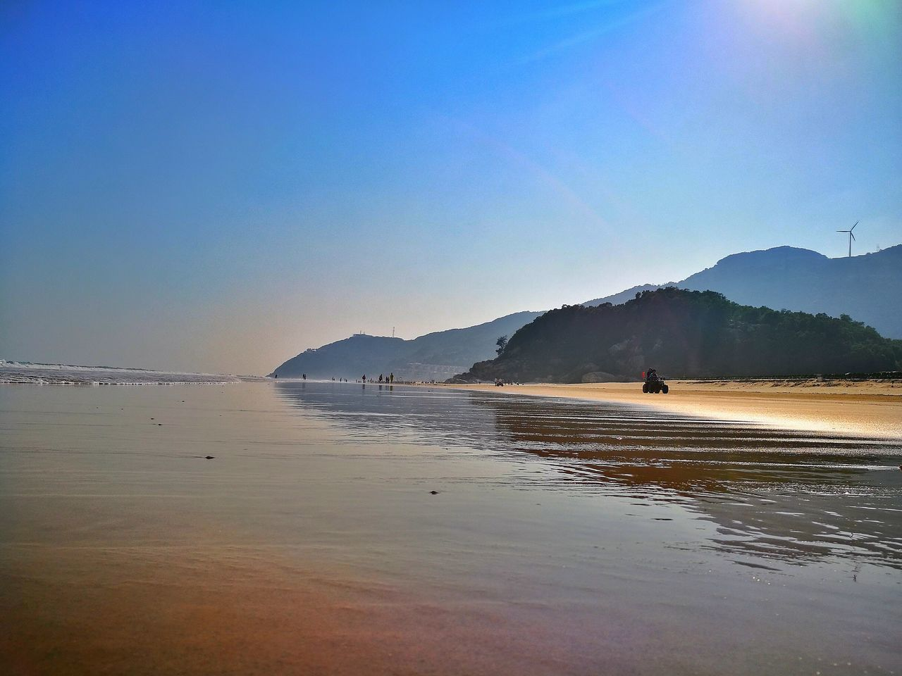 beach, sea, water, nature, beauty in nature, sand, scenics, clear sky, outdoors, vacations, tranquil scene, tranquility, mountain, blue, real people, sky, day, one person, men, people