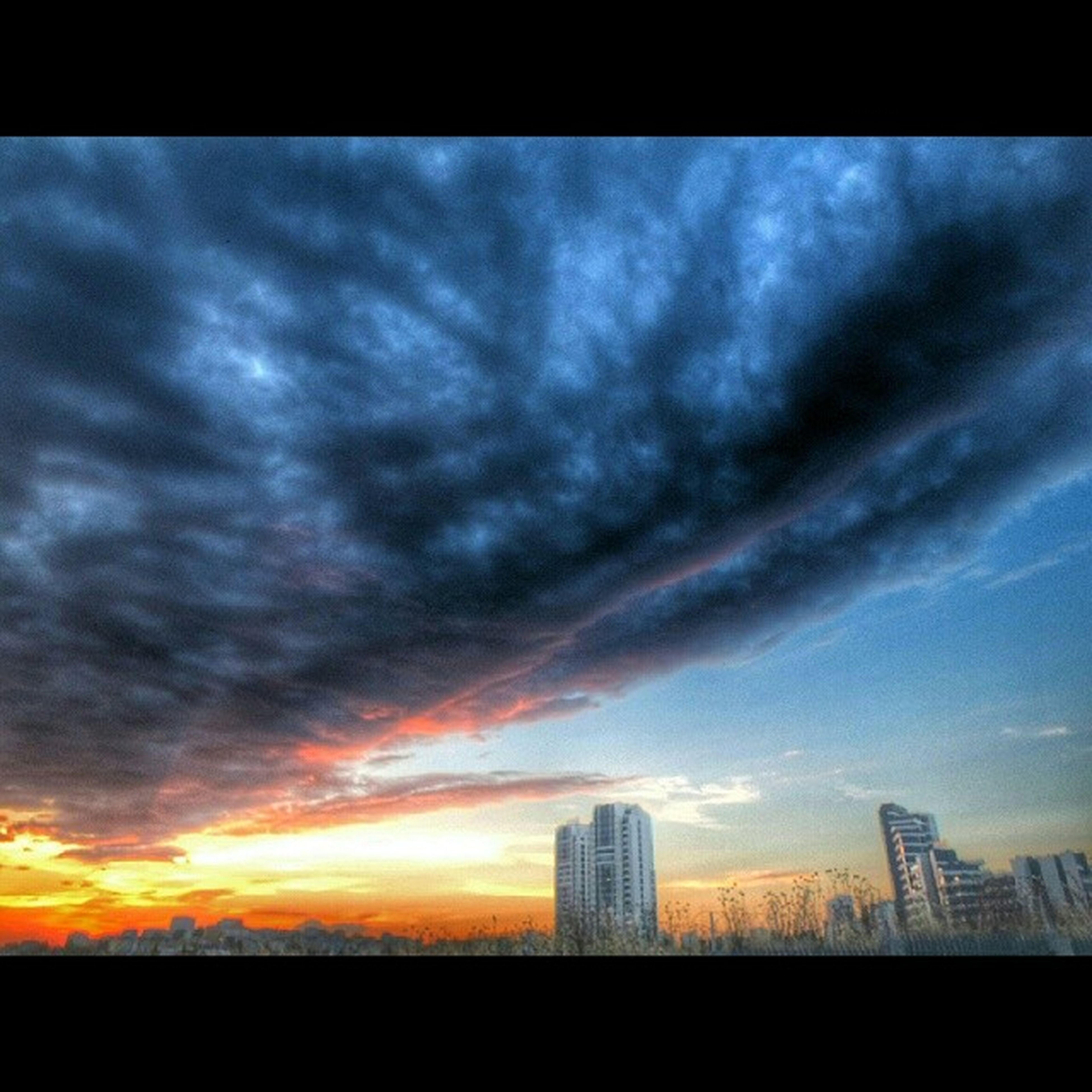 sunset, sky, building exterior, architecture, built structure, cloud - sky, silhouette, city, transfer print, skyscraper, cloudy, low angle view, cloud, auto post production filter, dramatic sky, orange color, tower, tall - high, weather, modern