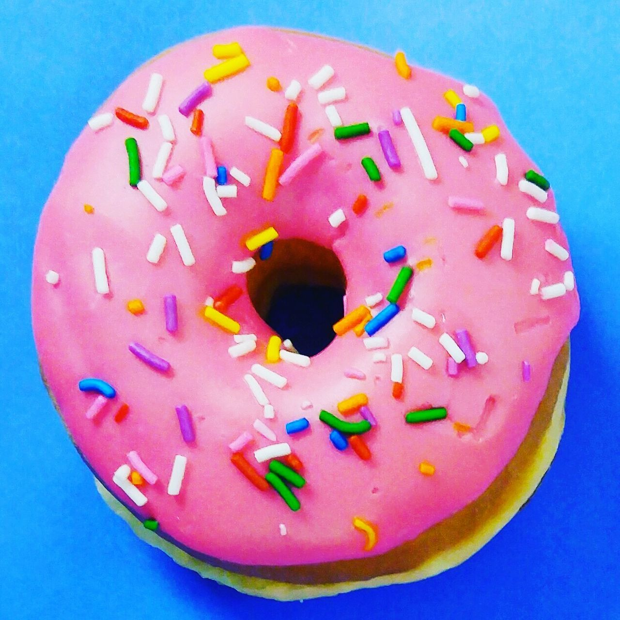 food and drink, food, unhealthy eating, indulgence, sprinkles, sweet food, studio shot, close-up, donut, high angle view, ready-to-eat, freshness, directly above, no people, multi colored, indoors, dessert, temptation, blue, anthropomorphic face, day
