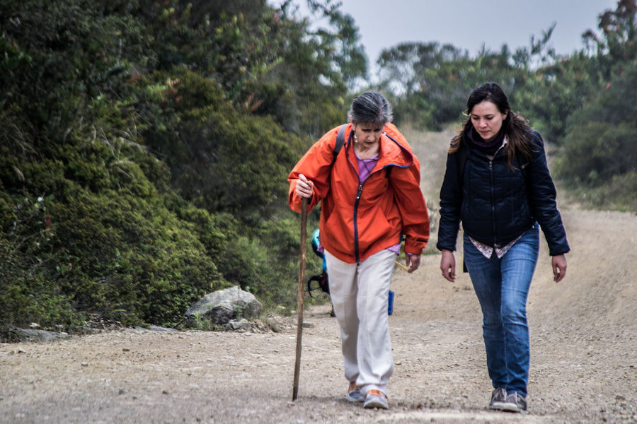 Trekking in Colombia Casual Clothing Colombia Escapism Friendship Full Length Leisure Activity Lifestyles Old Woman Outdoors Perspective Real People Rear View Standing Trekking TrekkingDay Walking Stick Women