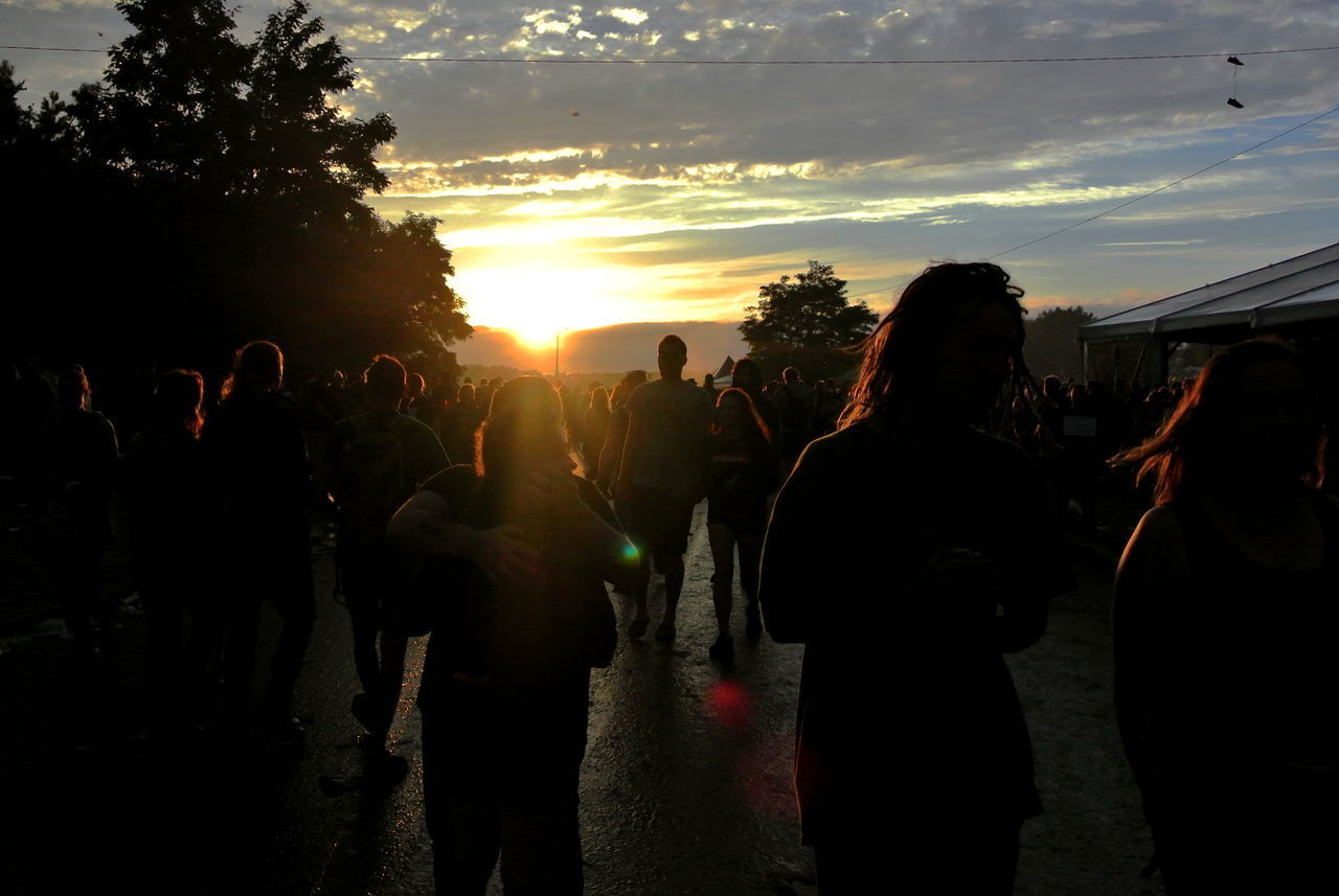 large group of people, sunset, leisure activity, sky, silhouette, togetherness, outdoors, real people, men, women, enjoyment, tree, sunlight, cloud - sky, lifestyles, crowd, nature, popular music concert, day, adult, people