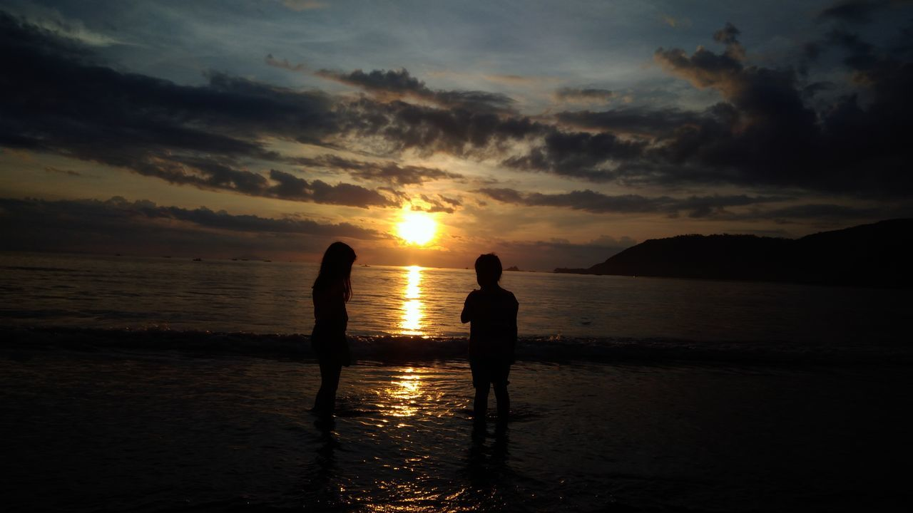 sunset, silhouette, beauty in nature, water, sky, sea, scenics, nature, cloud - sky, tranquility, tranquil scene, sun, reflection, beach, horizon over water, leisure activity, two people, vacations, real people, standing, outdoors, lifestyles, childhood