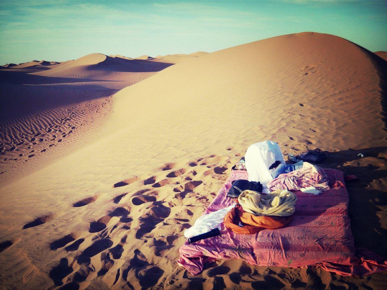 Mattress in desert against sky