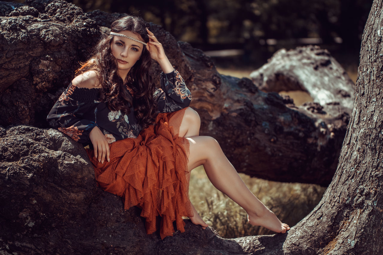 Young female hippie sitting on a big tree trunk Beautiful People Beautiful Woman Beauty Beauty In Nature Day Fashion Fashion Model Forest Long Hair Looking At Camera Nature One Person One Young Woman Only Outdoors People Portrait Real People Sitting Tree Tree Trunk Young Women