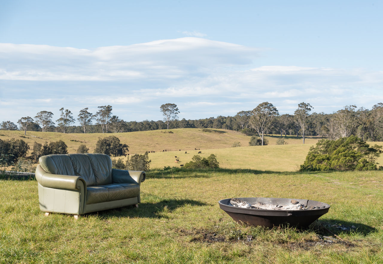 Outdoor living room - couch and fire pit in paddock with cows in background Beauty In Nature Cloud - Sky Day Field Grass Landscape Nature No People Outdoors Scenics Sky Tranquility Tree