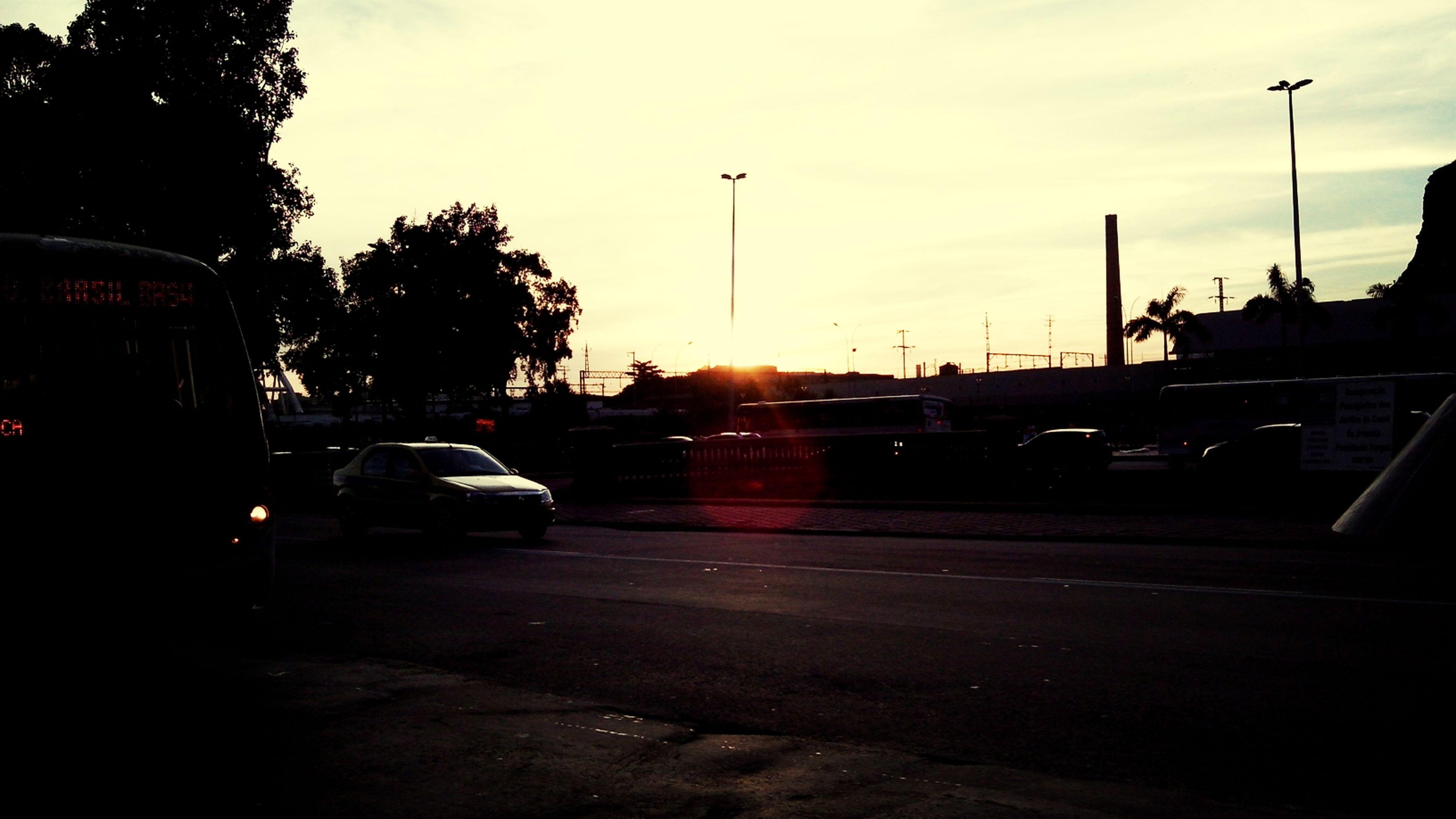 transportation, car, land vehicle, mode of transport, sunset, road, street, sky, tree, street light, silhouette, sun, the way forward, on the move, travel, traffic, sunlight, lens flare, cloud - sky, diminishing perspective