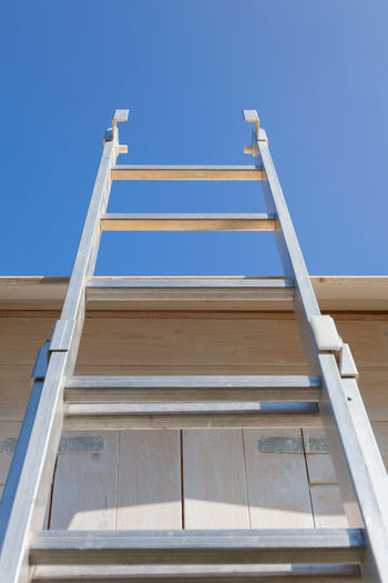 Ladder on three house Blue Built Structure Carpentry Clear Sky Construction Copy Space Cottage Crafts Craftsmanship  Growing Growth Hut Ladder No People Outdoors Tree House Wood - Material