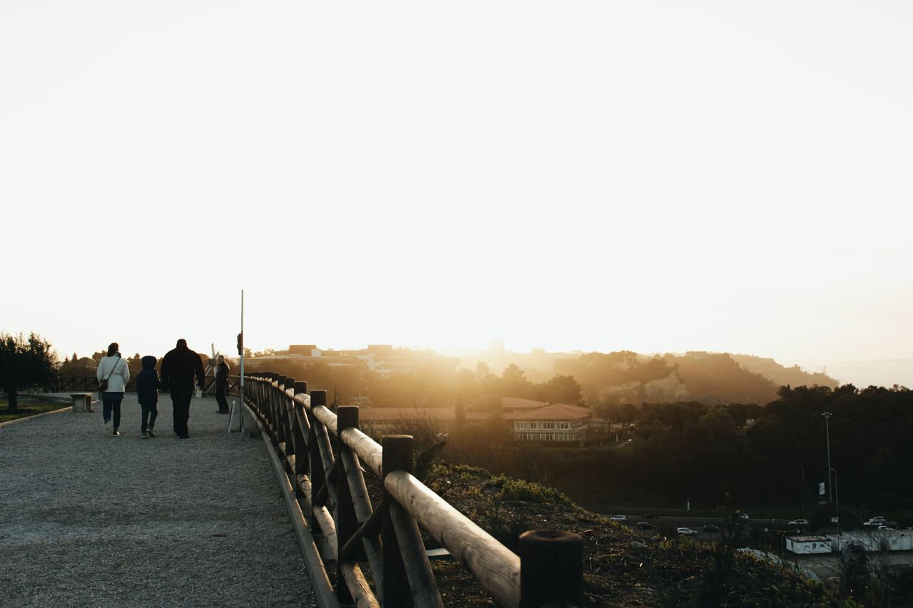 walking, real people, copy space, sunset, clear sky, men, outdoors, leisure activity, togetherness, nature, two people, lifestyles, built structure, women, sky, full length, architecture, city, friendship, day, beauty in nature, people