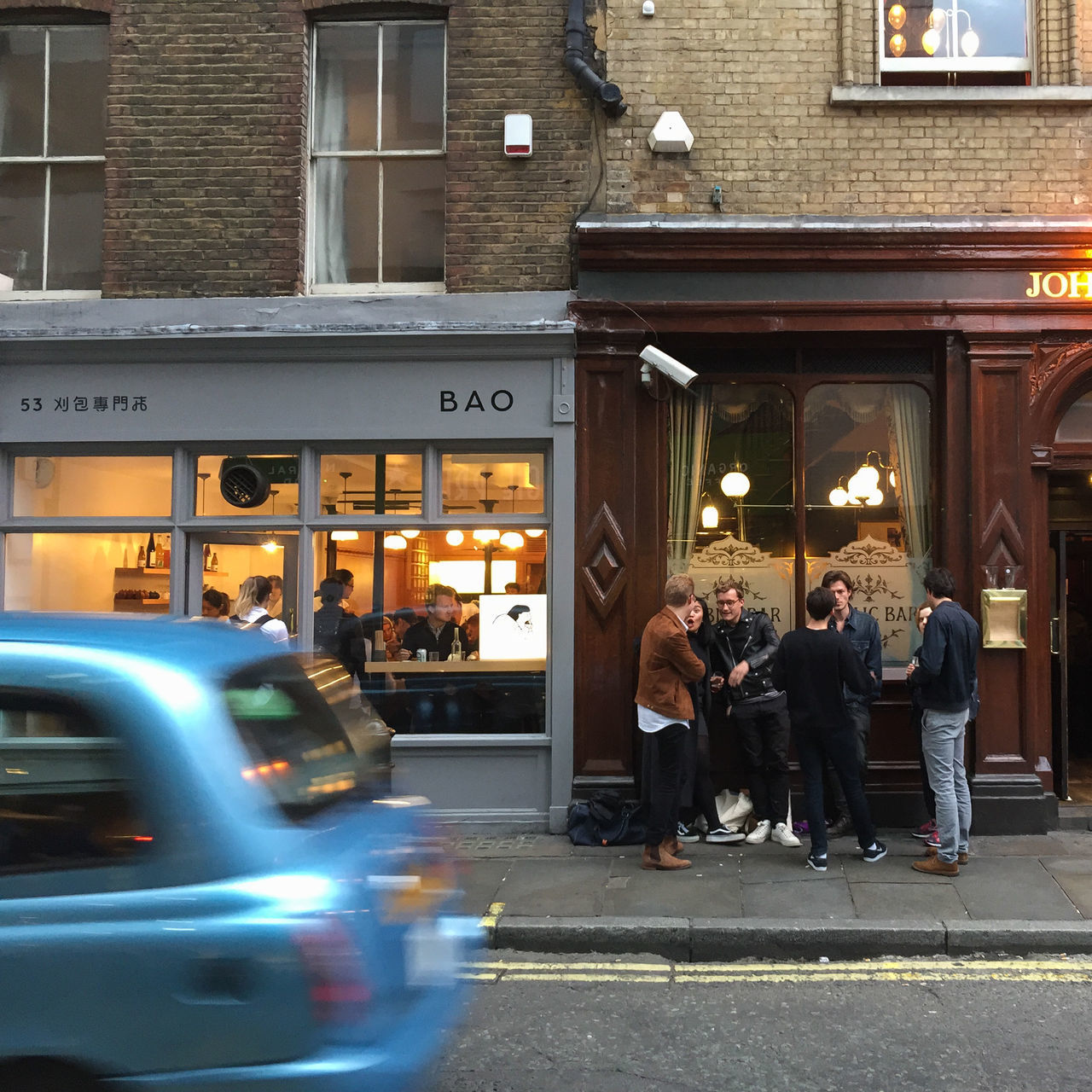 A group of friends in London hang out on a warm summer evening in front of John Snow Pub, next door to the popular restaurant Bao. Friends London Pub Sidewalk Adult Adults Only Architecture Building Exterior Built Structure Car City Day Editorial  Evening Leisure Activity Lifestyles Men Outdoors People Real People Restaurant Standing Street Togetherness Women