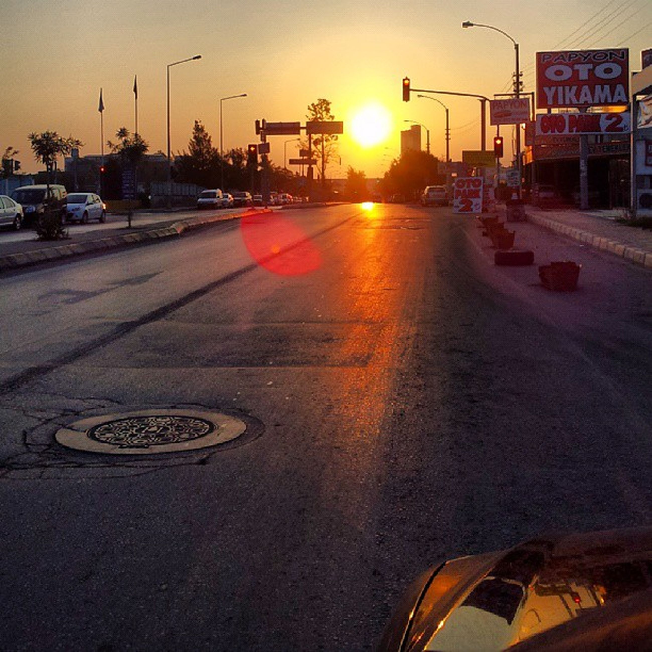 transportation, car, land vehicle, mode of transport, street, road, sunset, city, road marking, building exterior, traffic, city street, the way forward, sun, street light, built structure, architecture, sky, city life, travel